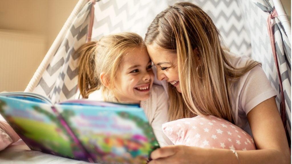 Mutter und Tochter lachen, während sie ihr vorliest