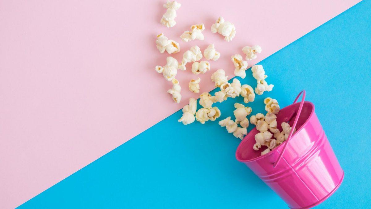Popcorn in einem rosa Eimer und auf einem rosa-blauen Hintergrund