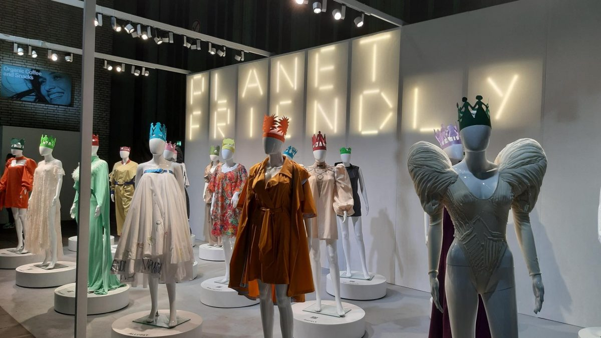 """Schaufensterpuppen eingekleidet in Kleider und Leuchtbuchstaben """"Planet Friendly"""" im Hintergrund"""