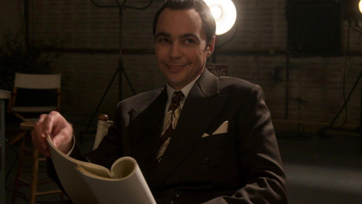 Schauspieler Jim Parsons lachend im Anzug mit Heft in der Hand