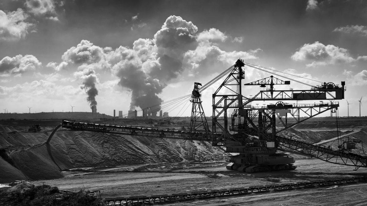 Schwarz weiß Fotografie von einer Kohlemine mit Windturbinen und Luftverschmutzung im Hintergrund