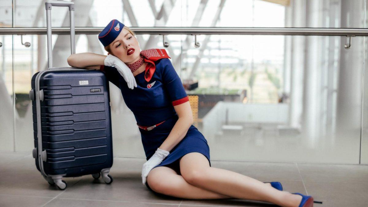 Stewardess sitzt an einen Koffer gelehnt