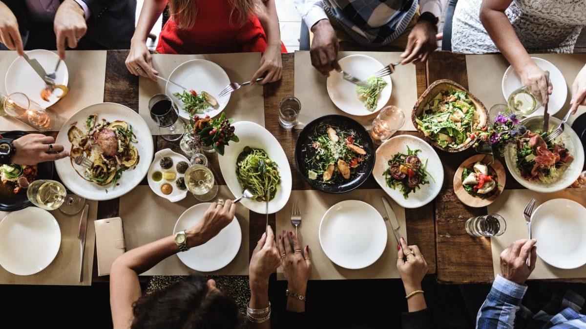 Tisch mit Speisen und Menschen, die sich daran bedienen