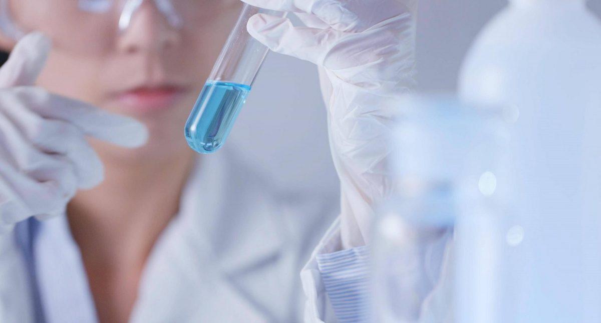 Wissenschaftlerin hält Reagenzglas mit blauer Flüssigkeit in Luft