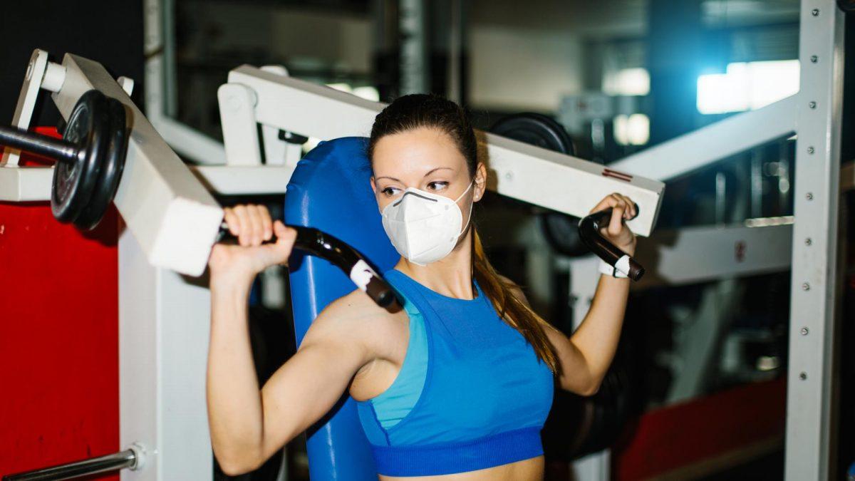 frau gym maske mundschutz gewichte sport fitness muskeln
