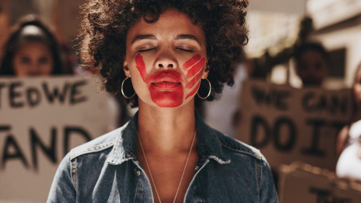 hübschre Frau mit Locken und rot geschminkter Hand im Gesicht auf einer Demo