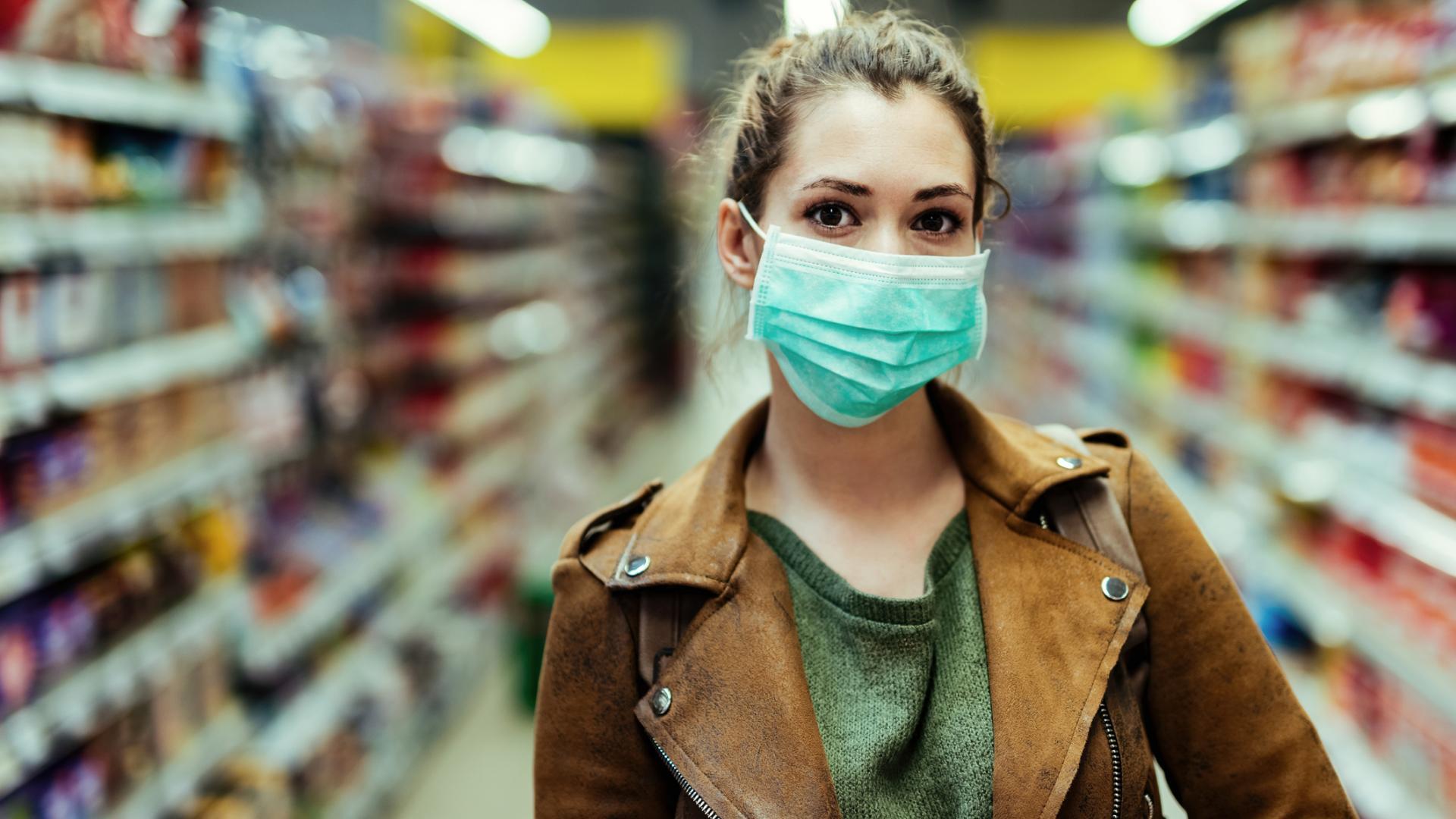 junge Frau einkaufen Corona Maske