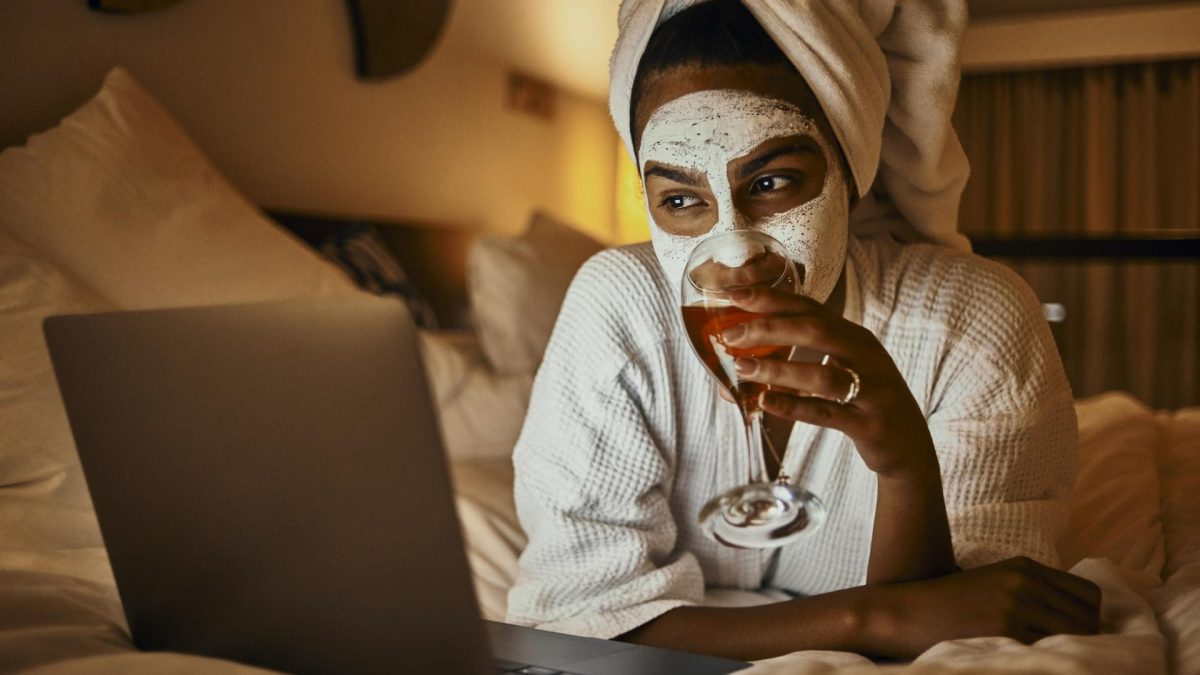 junge Frau entspannt im weißen Bademantel mit Gesichtsmaske schaut Netflix