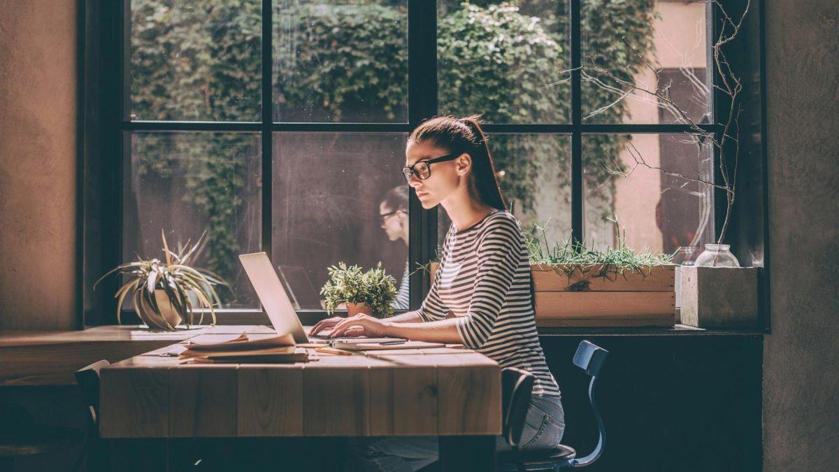 junge Frau mit Brille sitzt an vor einem Laptop am Fenster in einem Büro oder Café