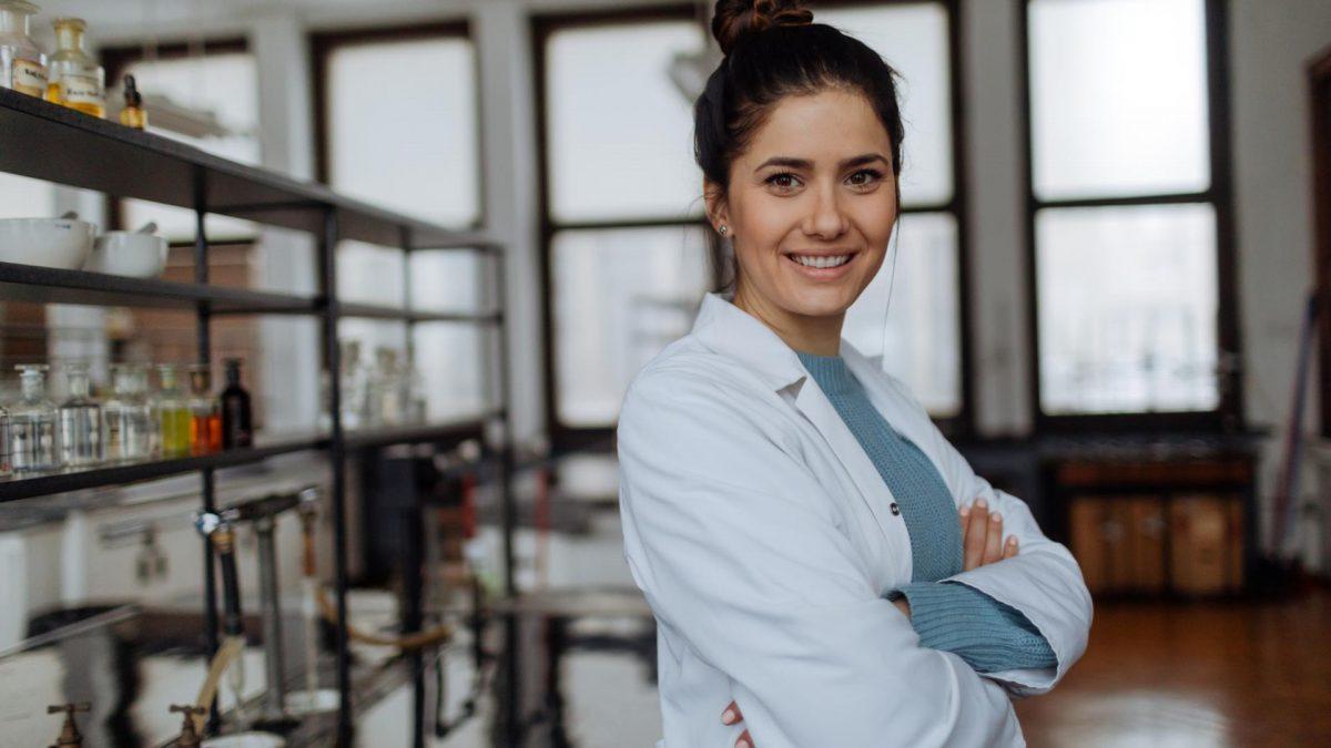 lächelnde Forscherin in Chemie Labor