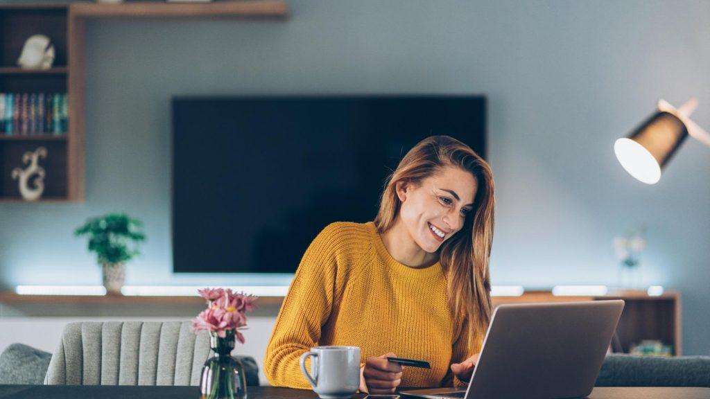 lächelnde Frau beim Online Shopping Zuhause vor dem Laptop