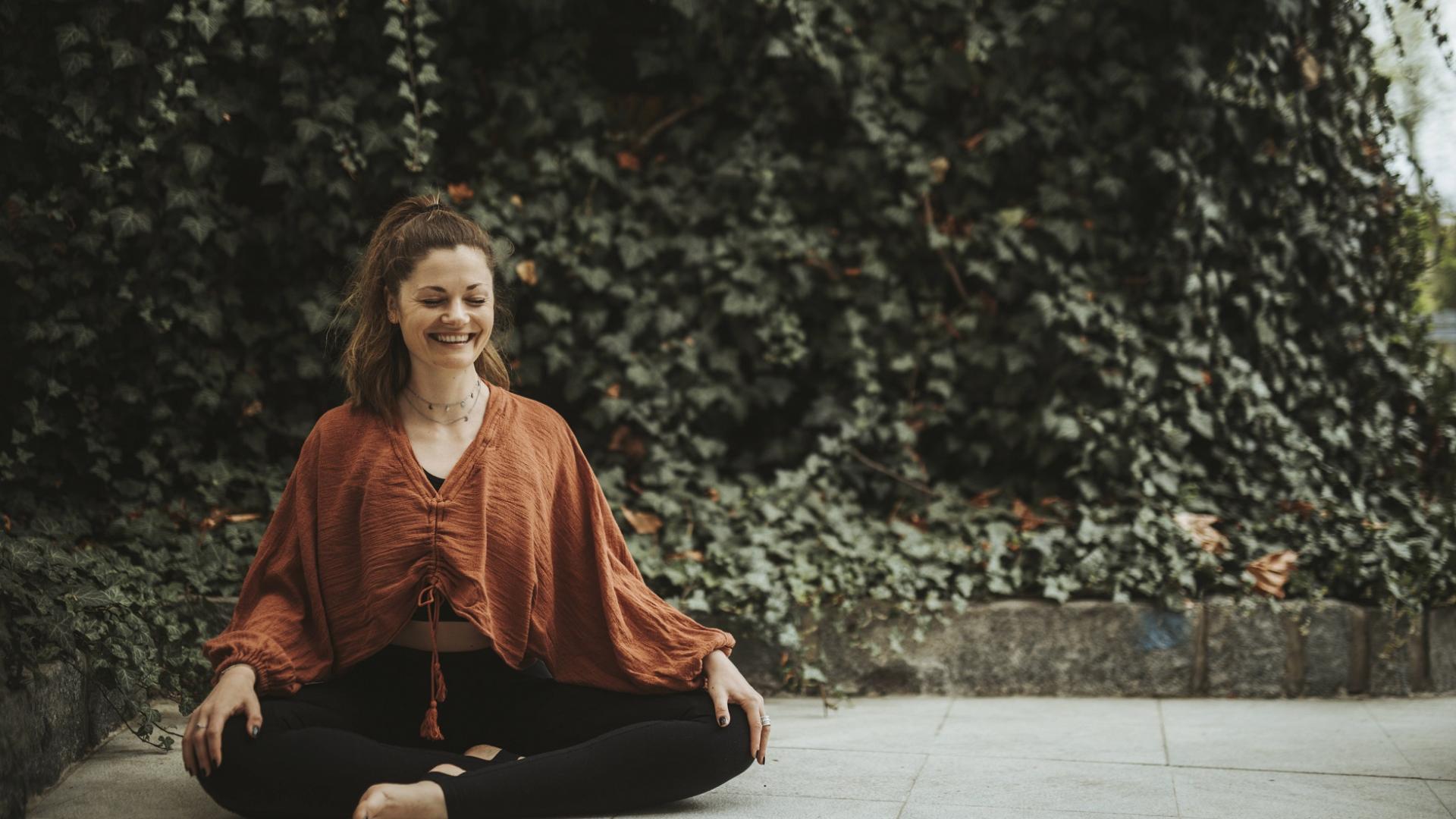 lächelnde Frau meditiert im Garten