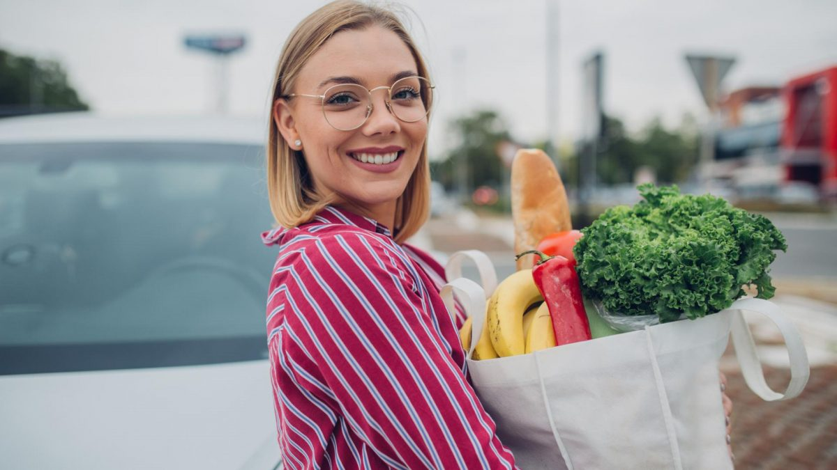 lächelnde Frau mit gestreifter Bluse mit Einkaufsbeutel in der Hand
