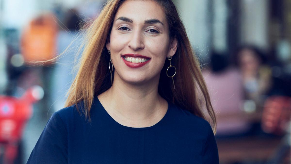 lächelnde dunkelhaarige Frau mit roten Lippen und dunkelblauen Oberteil