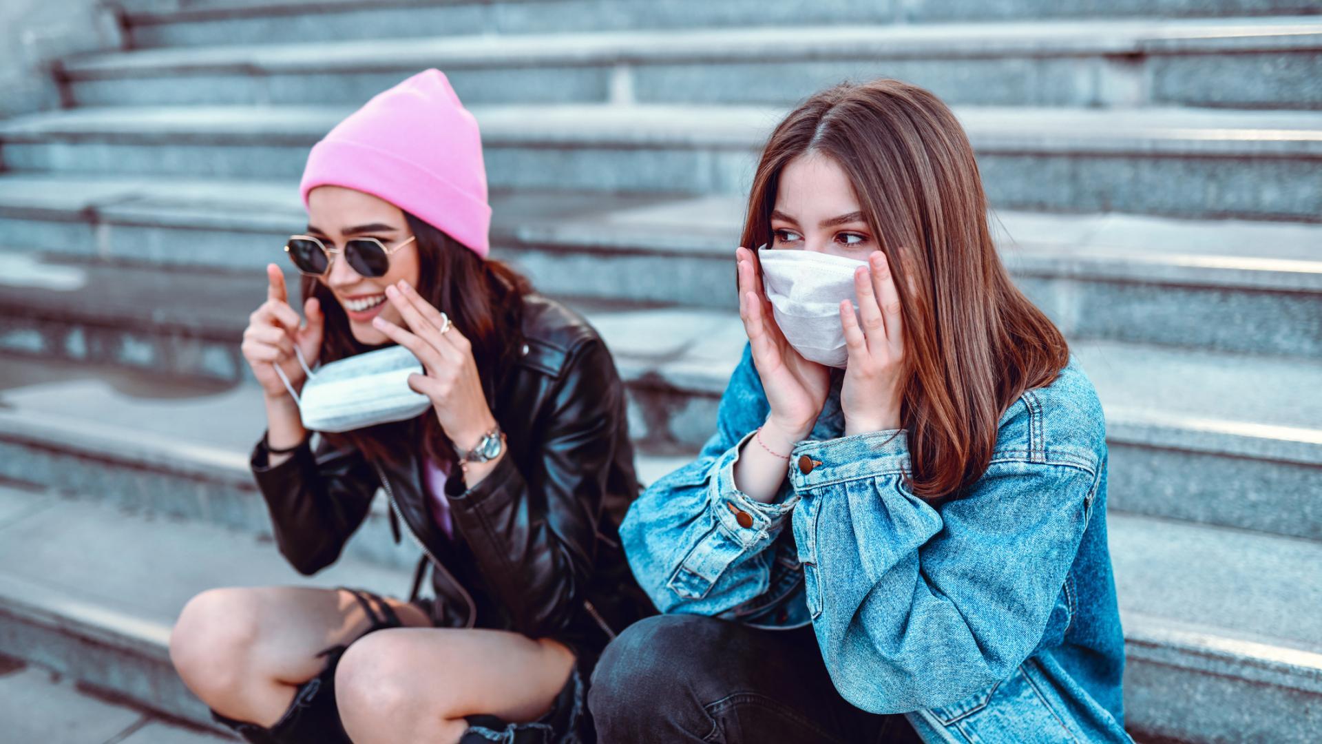 zwei junge Frauen tragen Masken