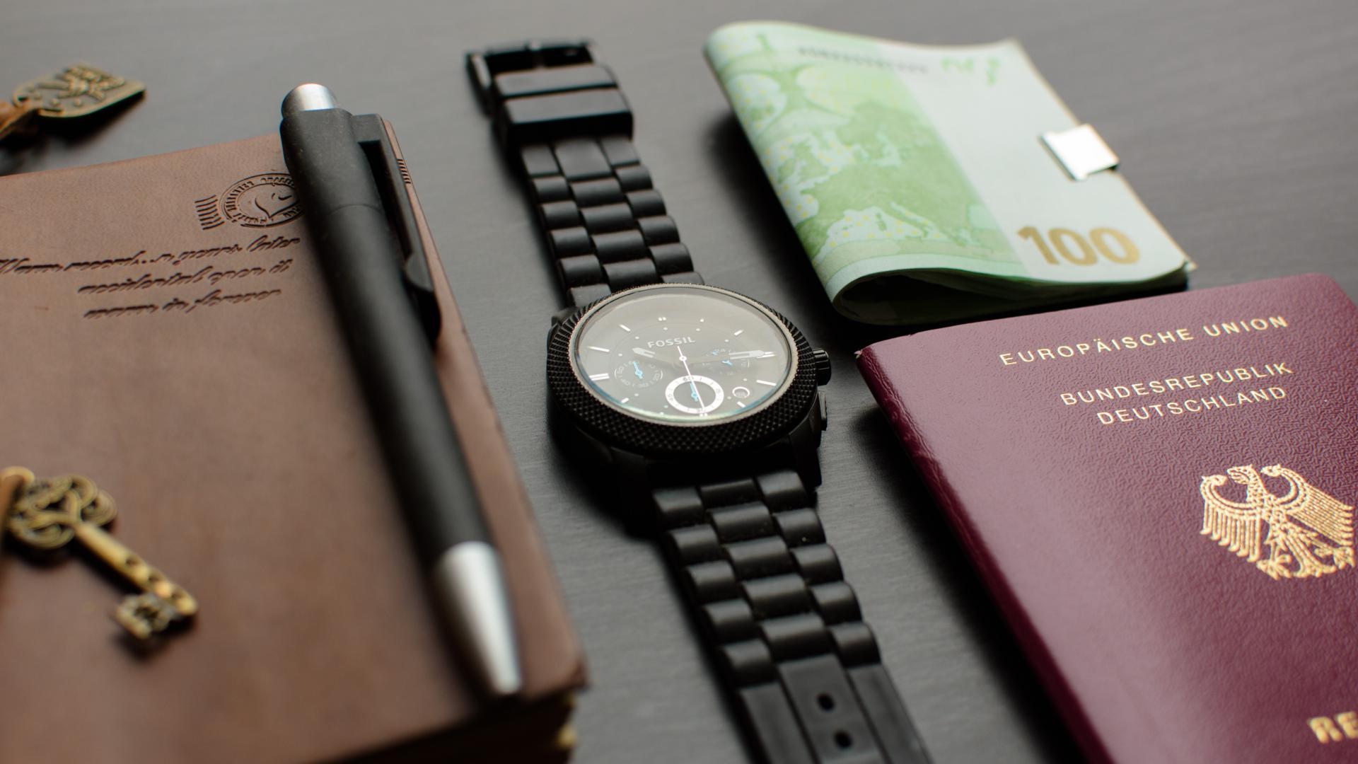Reisepass, Uhr, Geld und Tagebuch auf einem Tisch