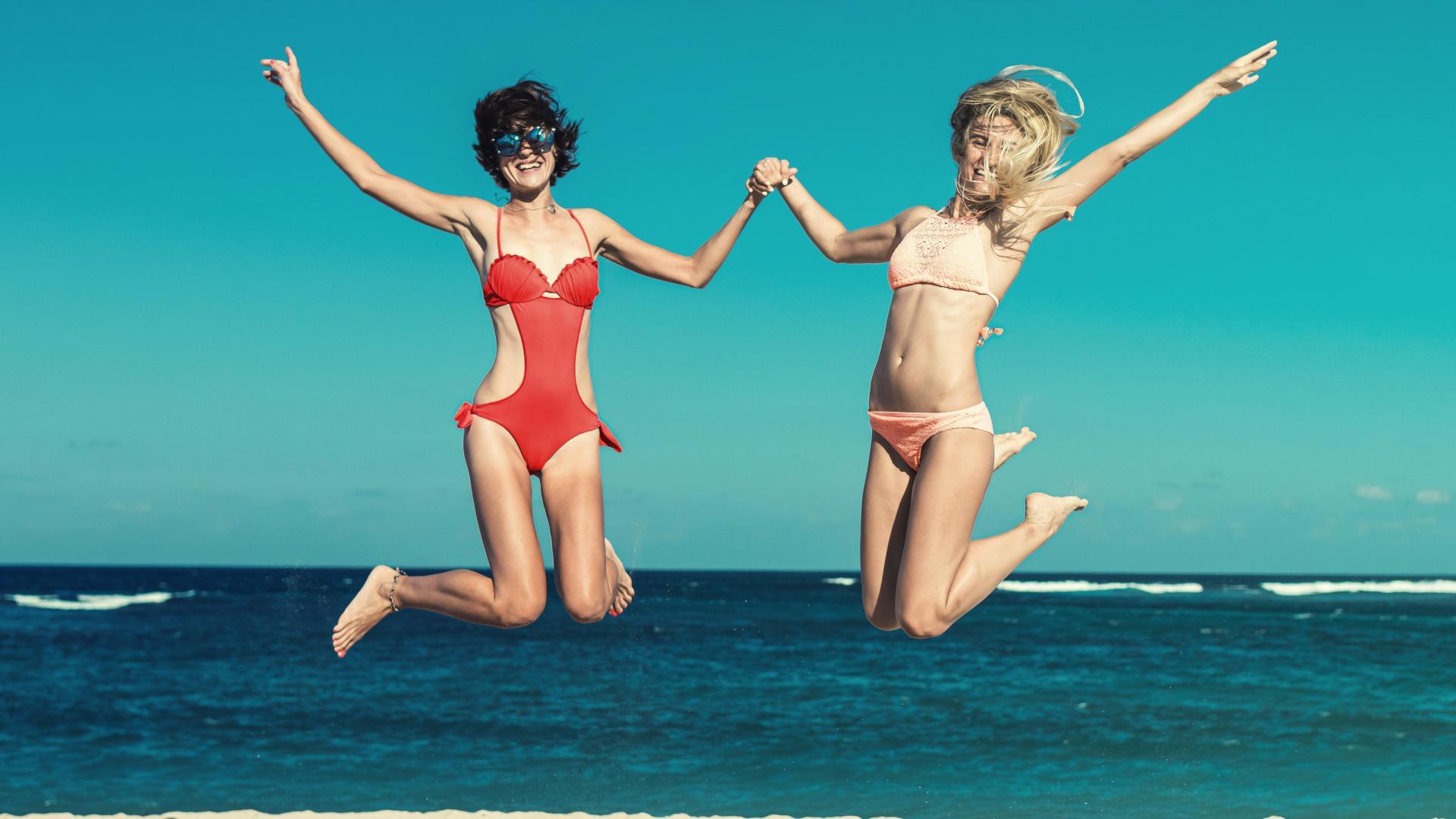 Zwei Freundinnen springen vergnügt hoch am Strand