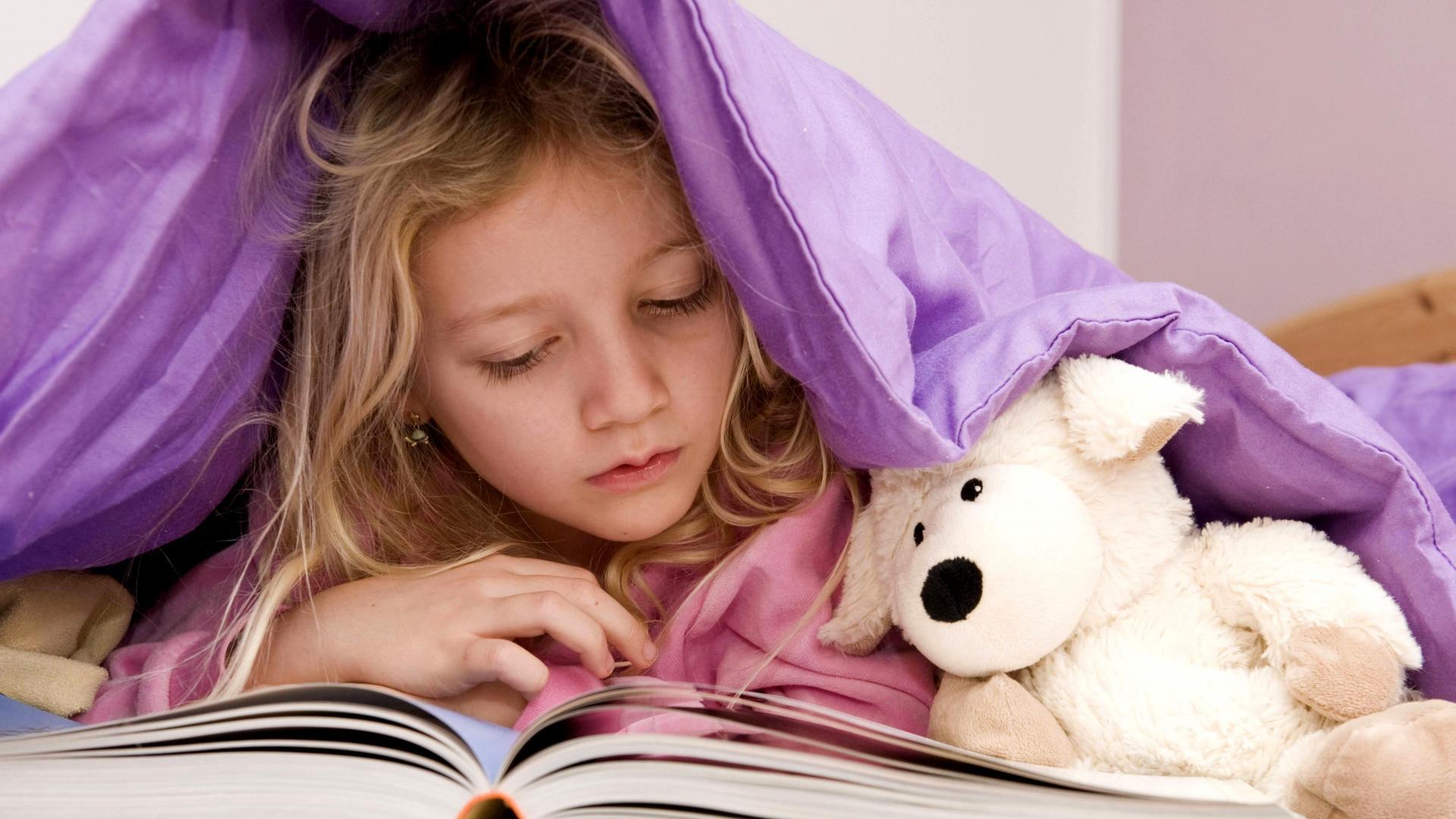Mädchen liegt unter der Bettdecke und liest ein Buch