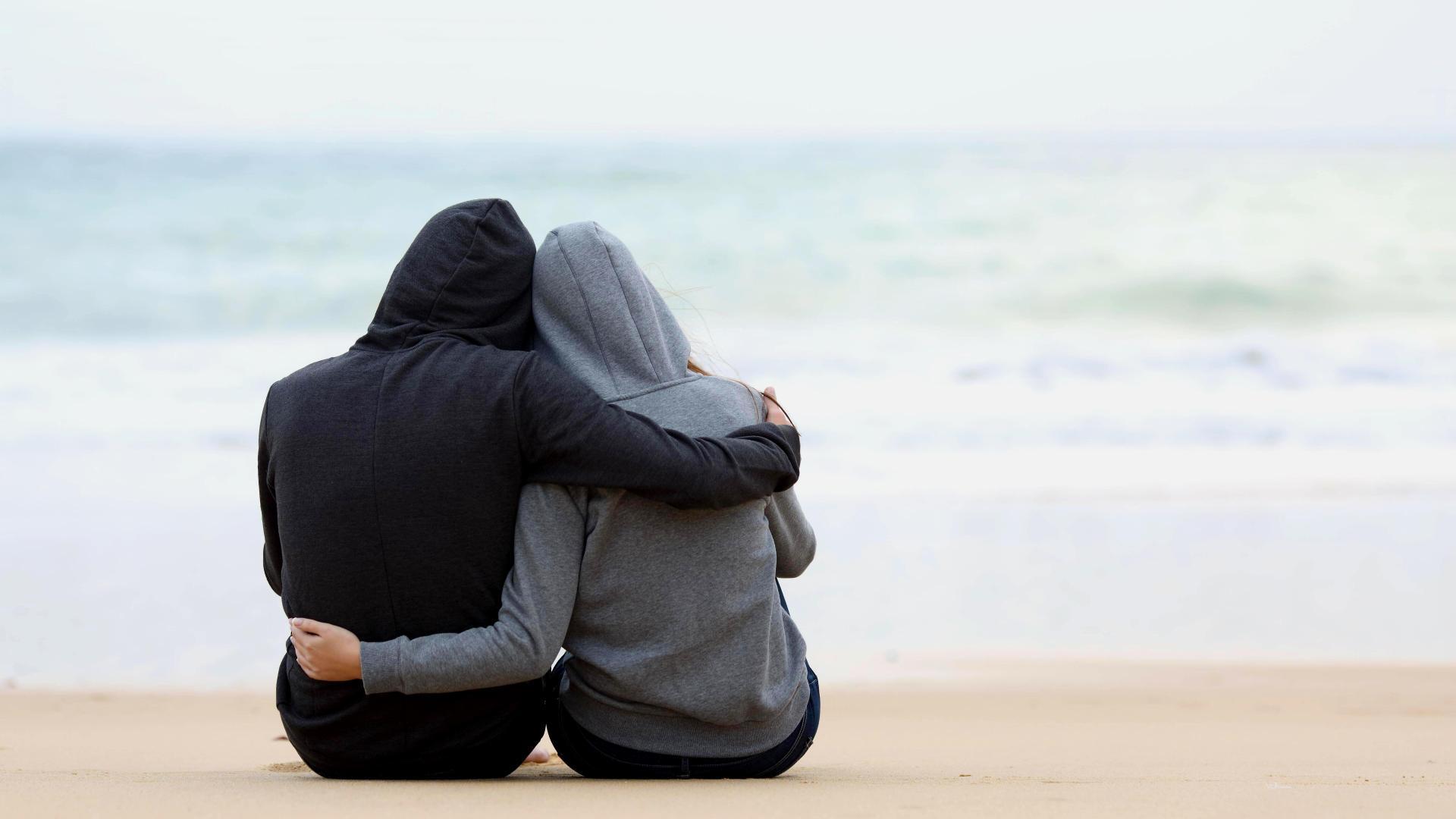 Pärchen sitzt am Strand, einsam und Arm in Arm