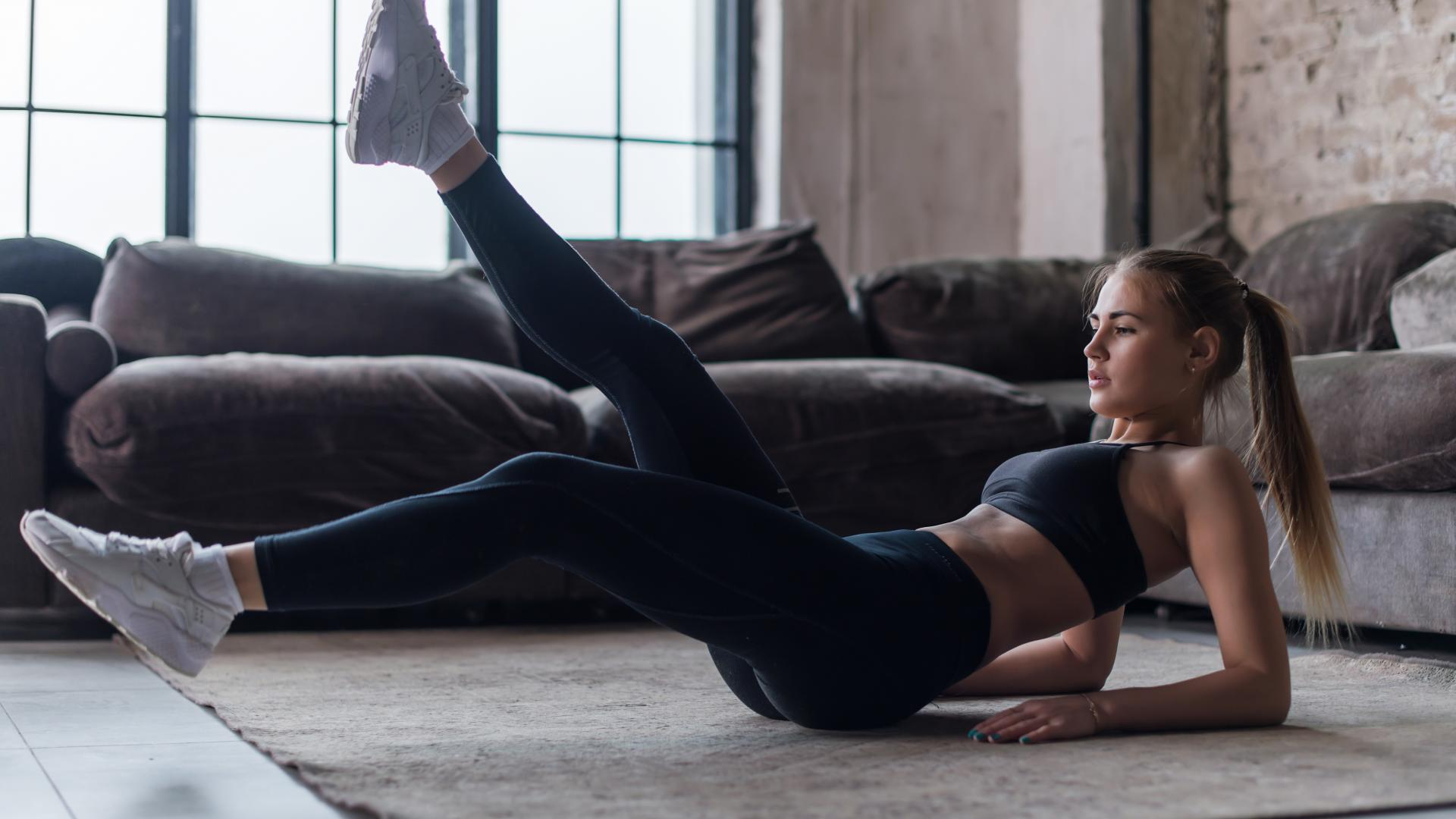 Young sporty female doing abs workout in living room performing alternate leg raising and crunch exercise.