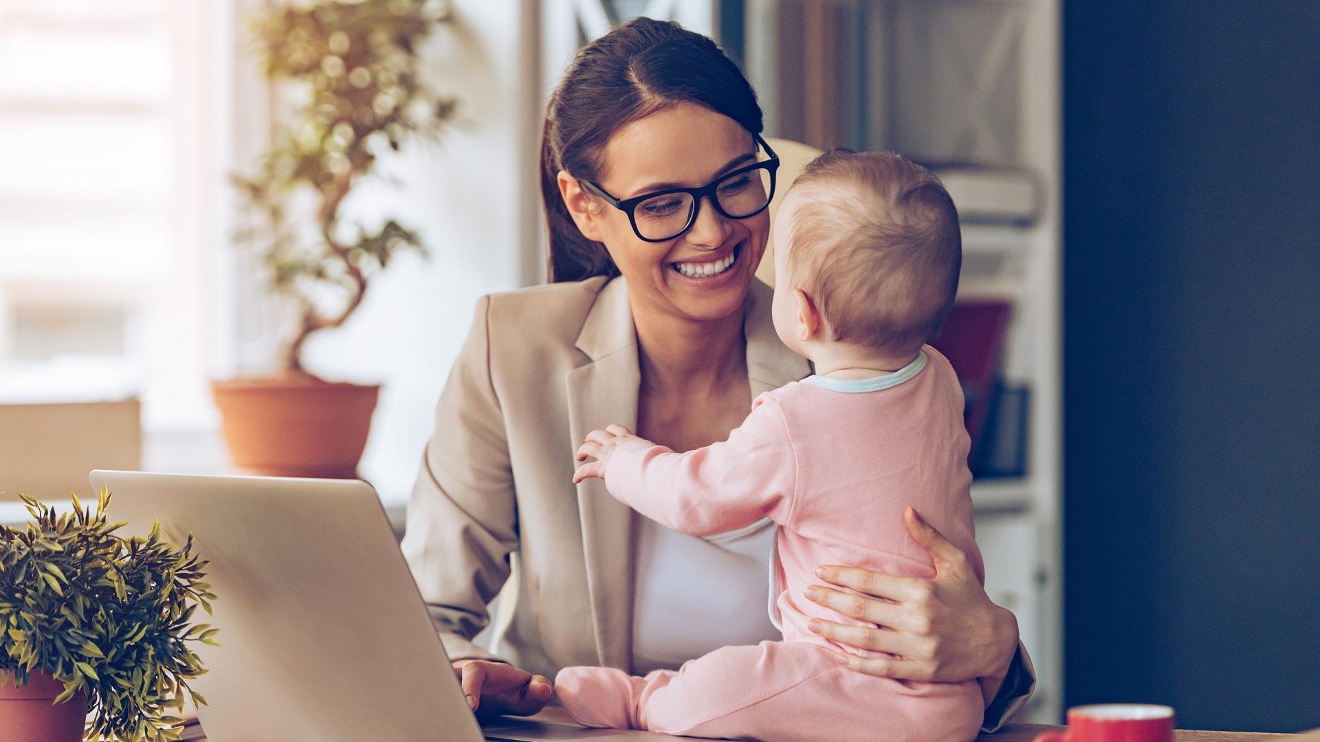 Frau sitzt vor einem Laptop mit Baby daneben