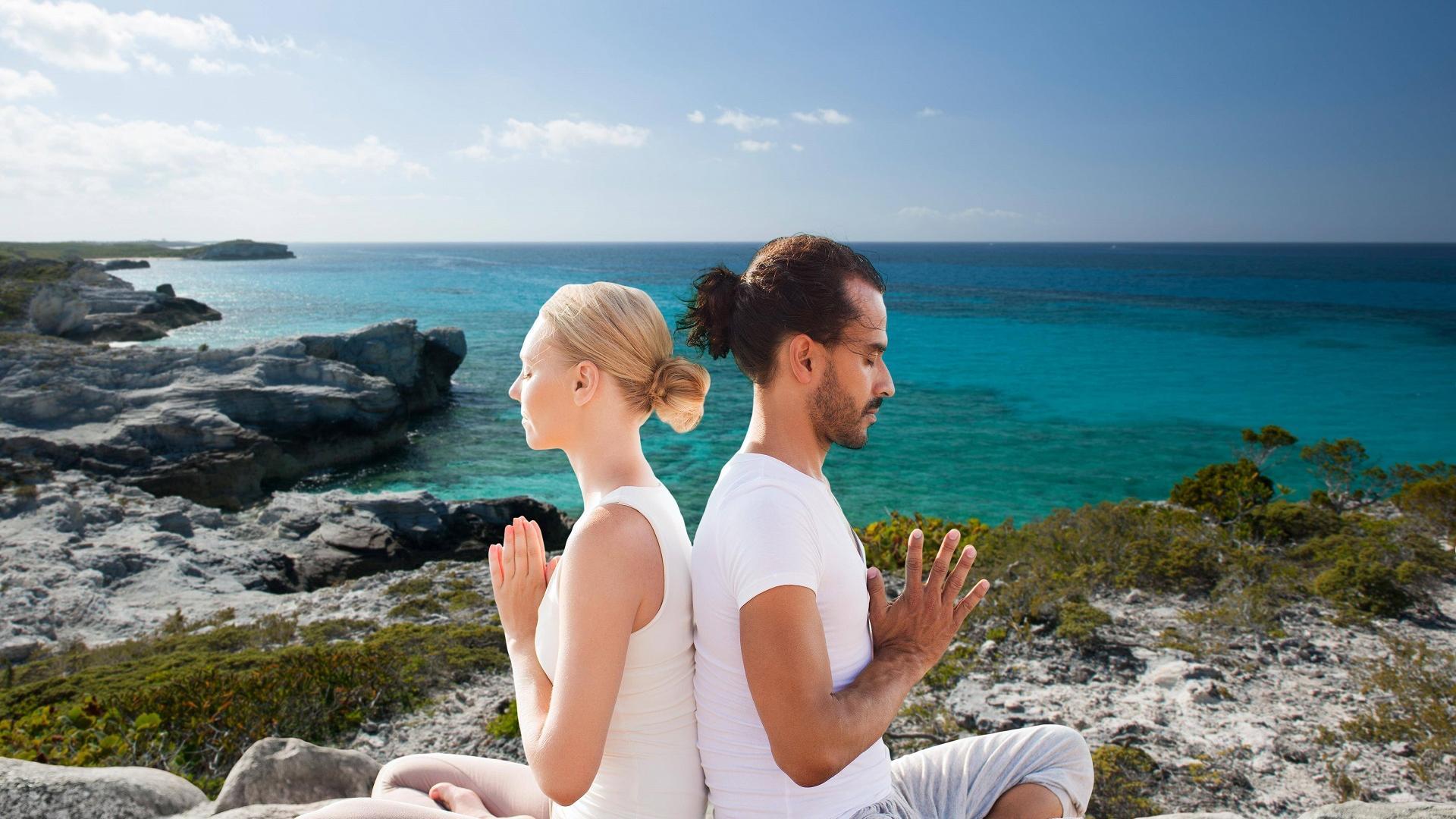 Pärchen sitzt Rücken an Rücken beim Partneryoga und meditiert