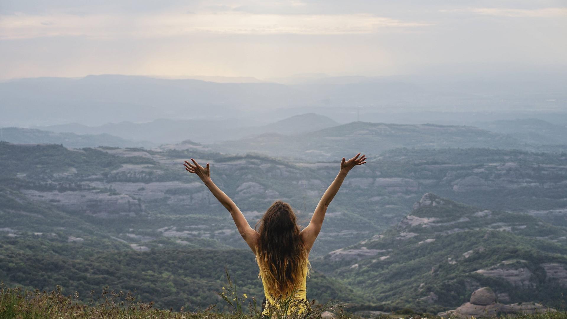 Frau am Berg, die Arme in die Luft streckt