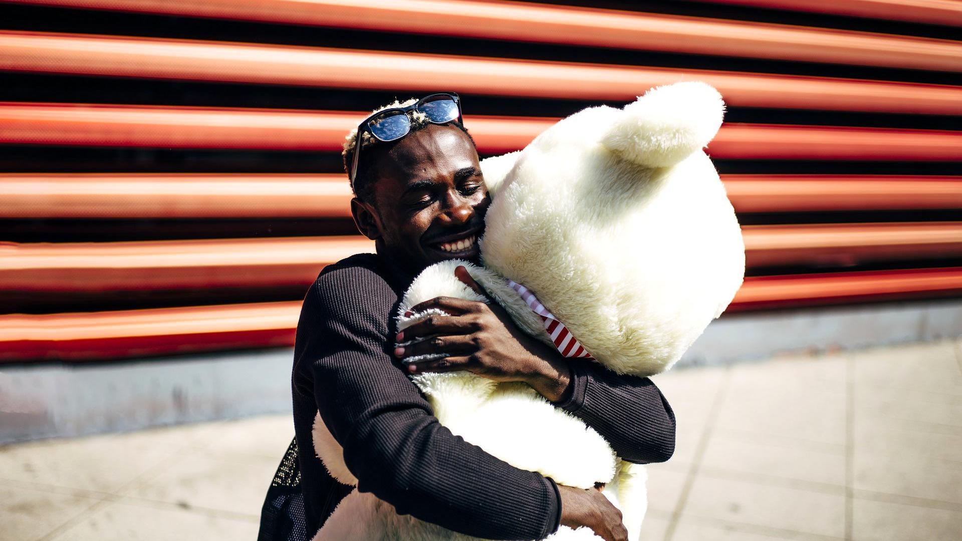 Mann der einen Bären kuschelt