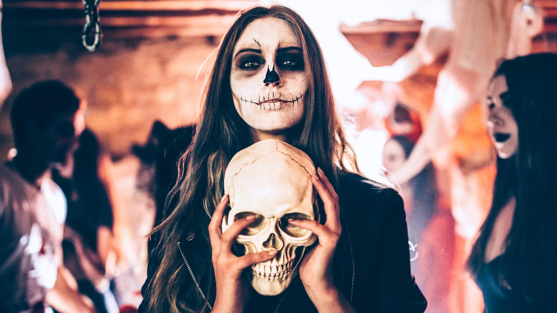 Totenkopf Frau hält einen Schädel in der Hand auf einer Halloweenparty