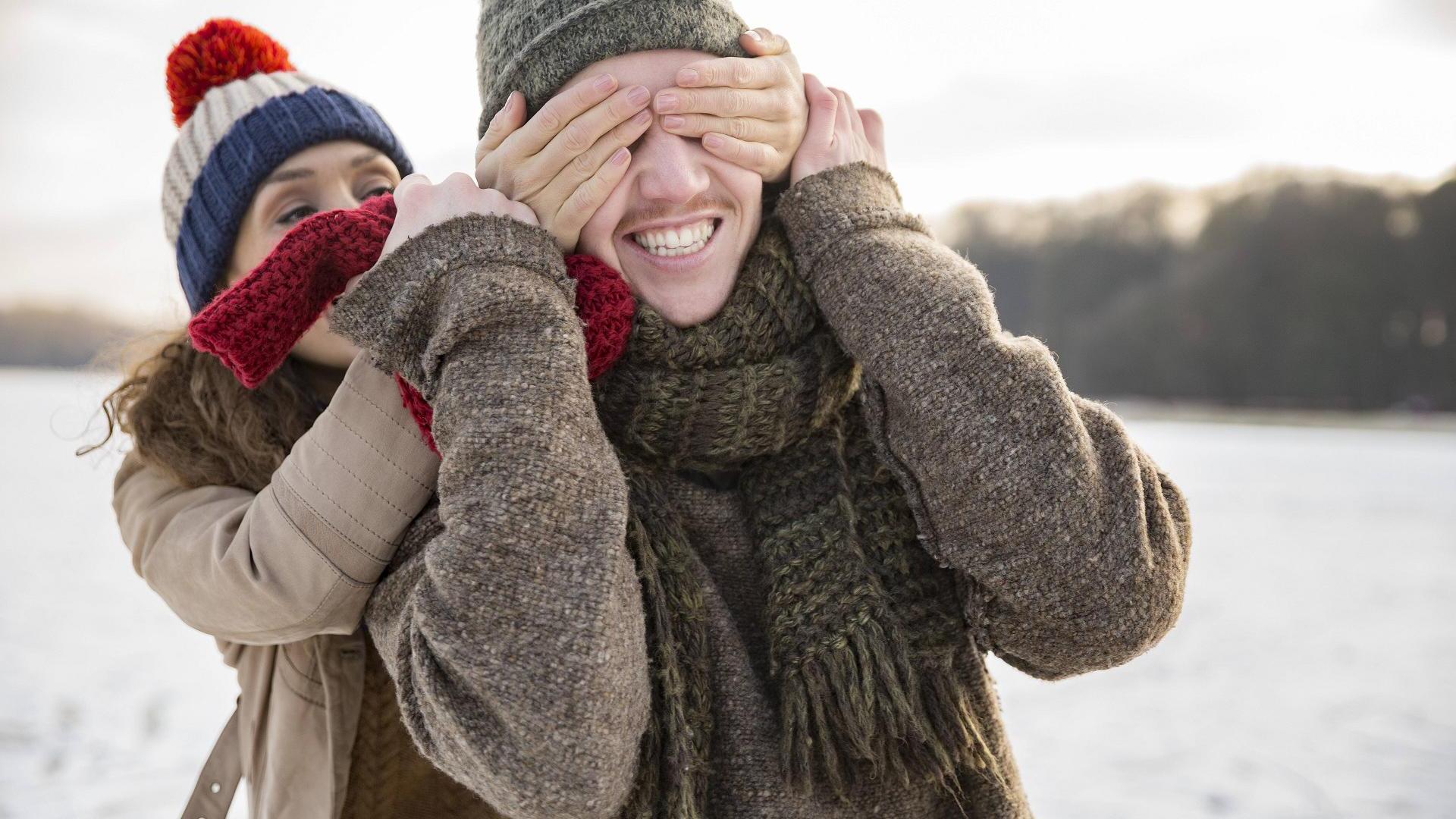 Pärchen im Winter überrascht sich, sie hält ihm die Augen zu