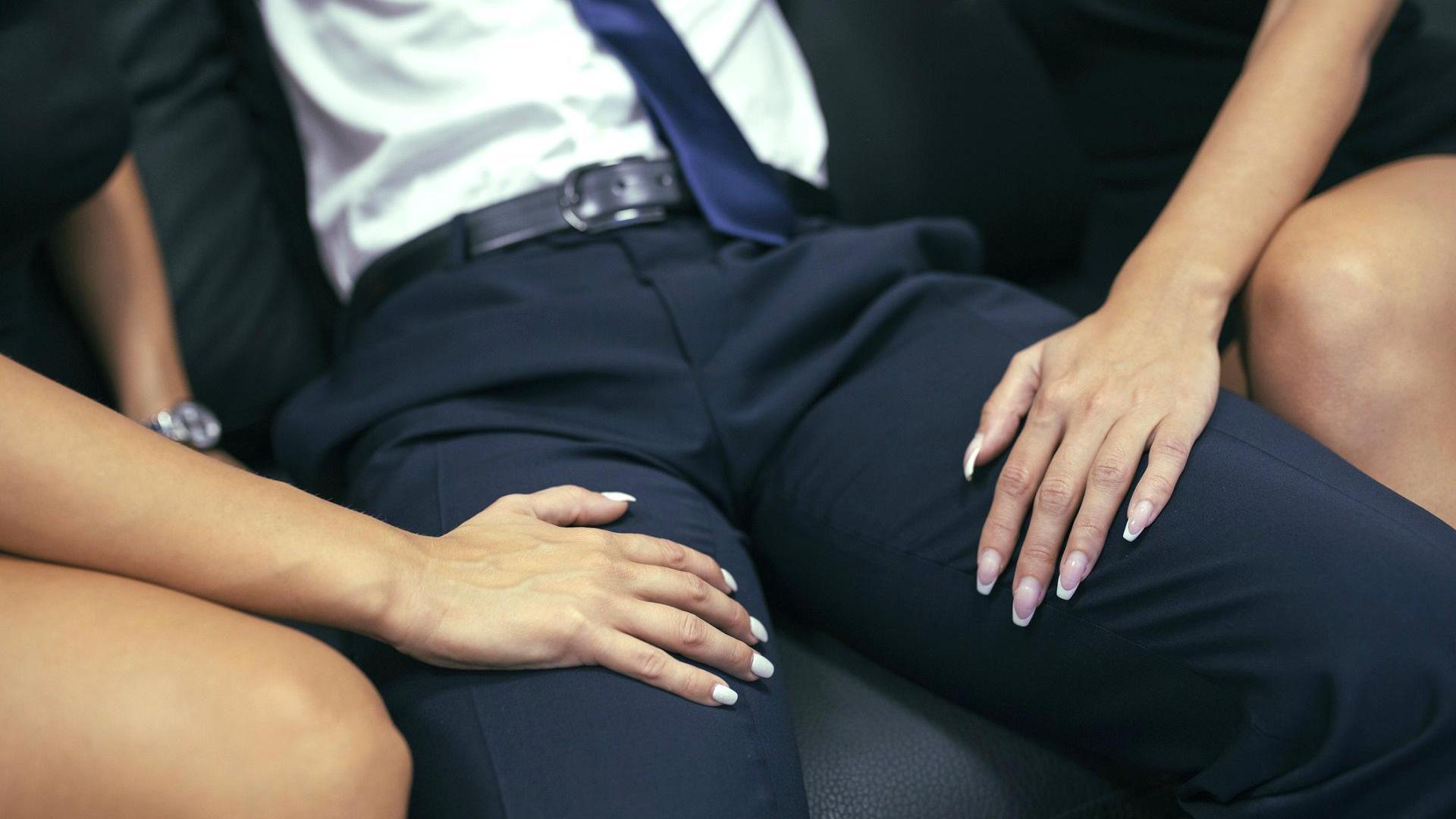 Zwei Frauen haben ihre Hände auf den Beinen eines Mannes