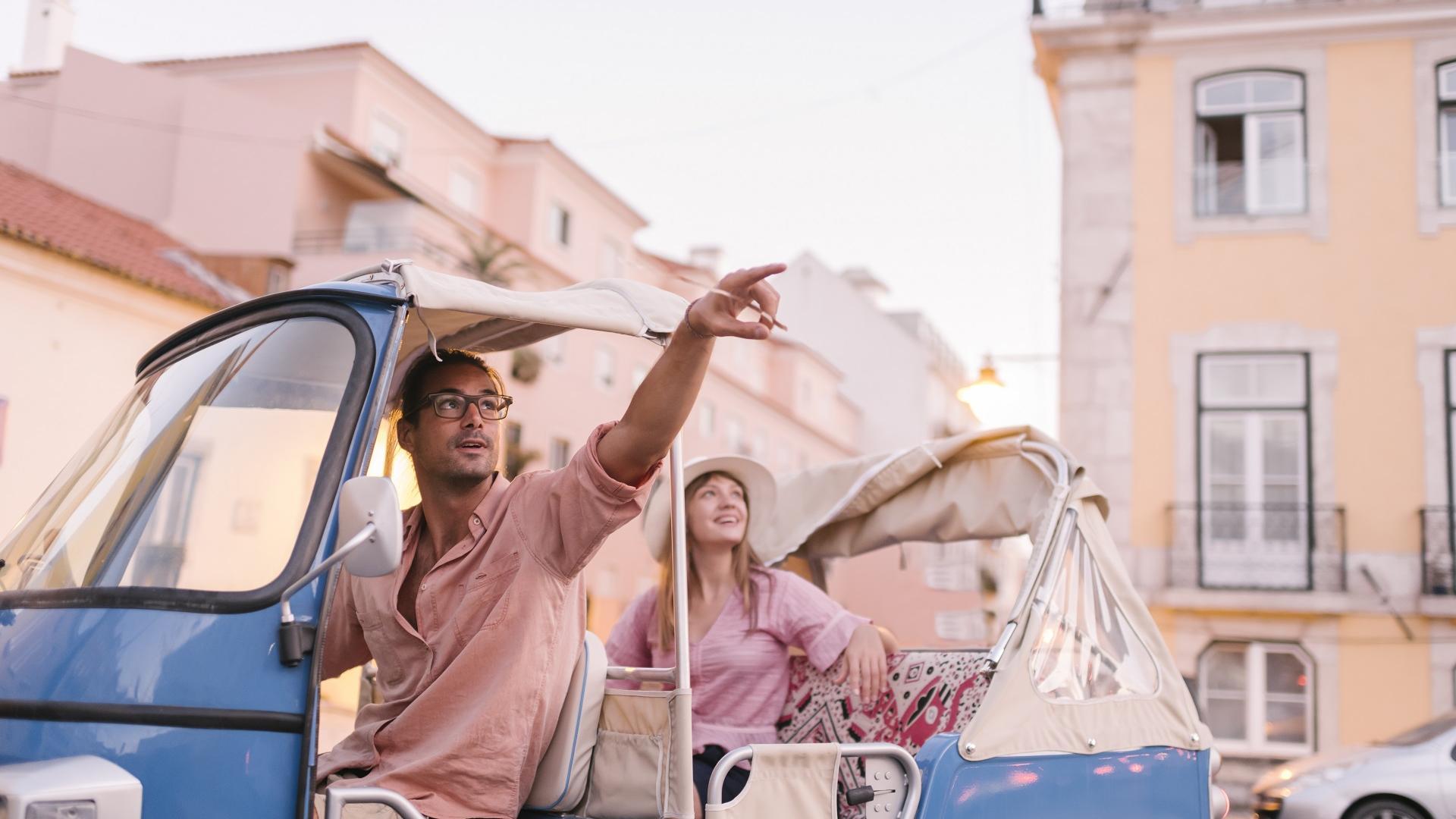 Mann sitzt in einem Taxi und deutet in die Luft, die Frau dahinter folgt seinem Blick