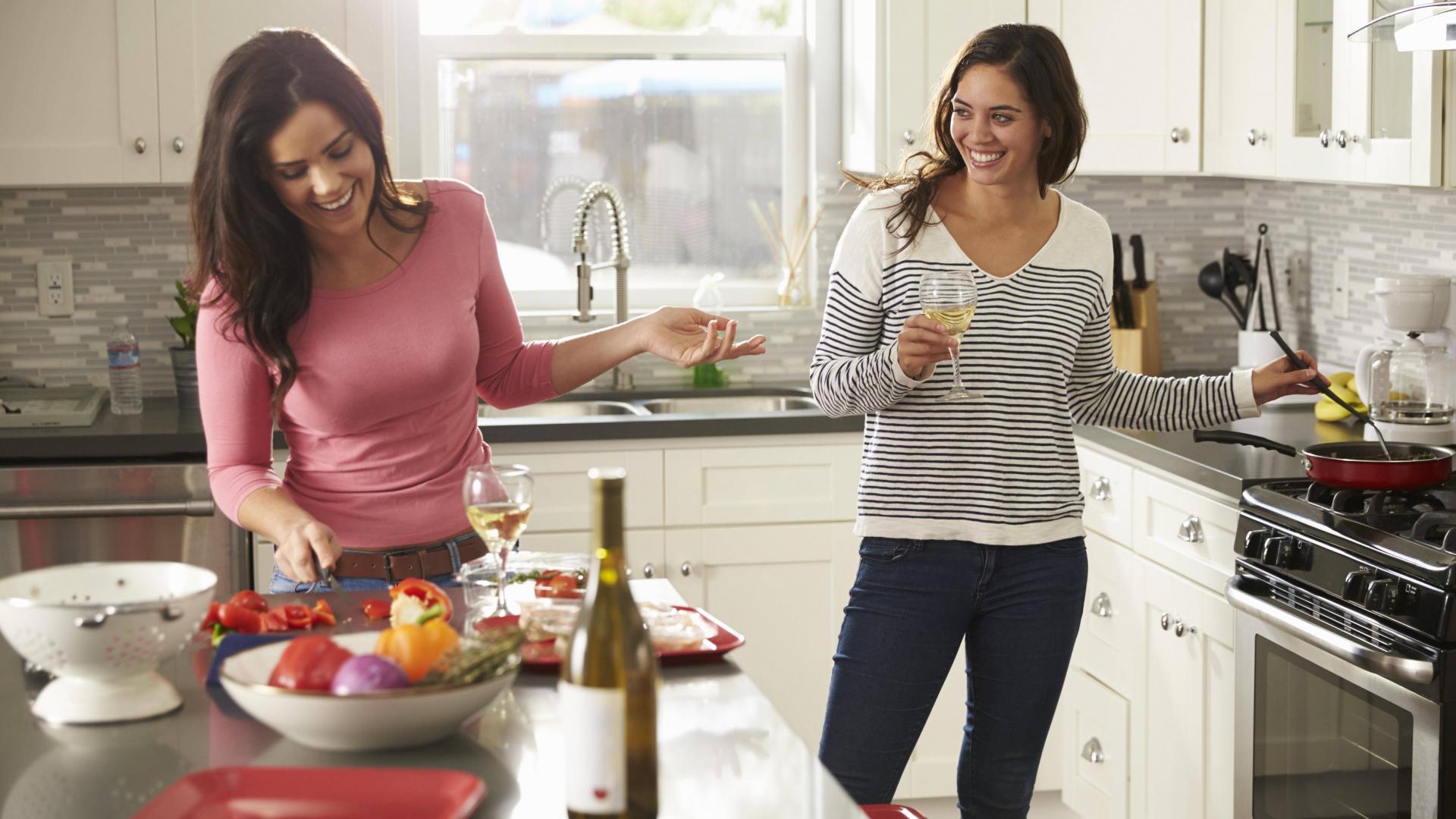 Frauen kochen zusammen und trinken Wein