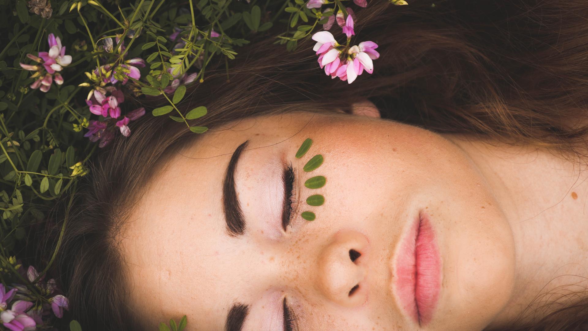 Frau auf einer Wiese mit Blättern im Gesicht