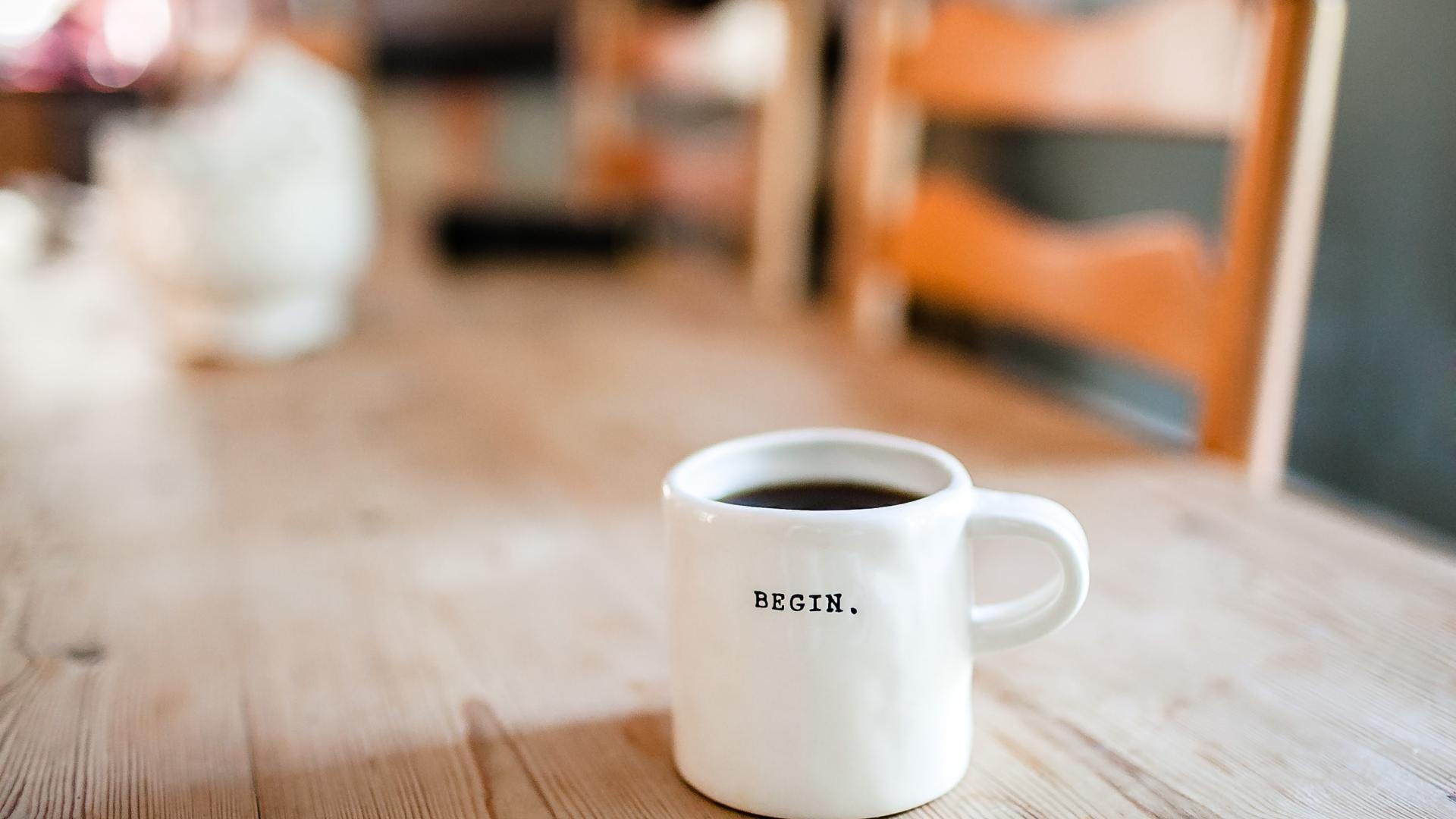 Tasse auf dem Holztisch mit der Aufschrift begin