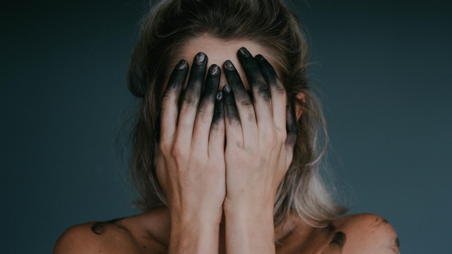 Frau mit schwarz gefärbten Fingern hält sich die Hände vor das Gesicht