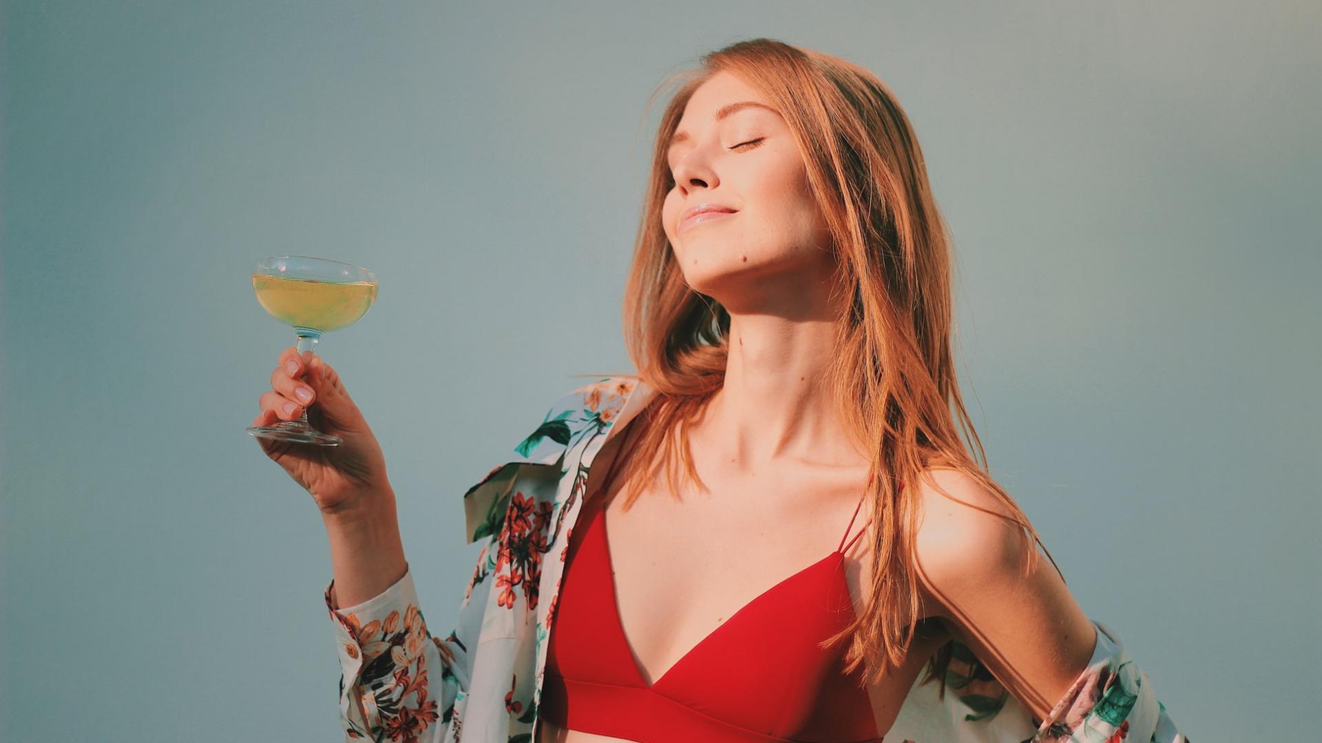 Frau blond mit Cocktail in der Hand im BH