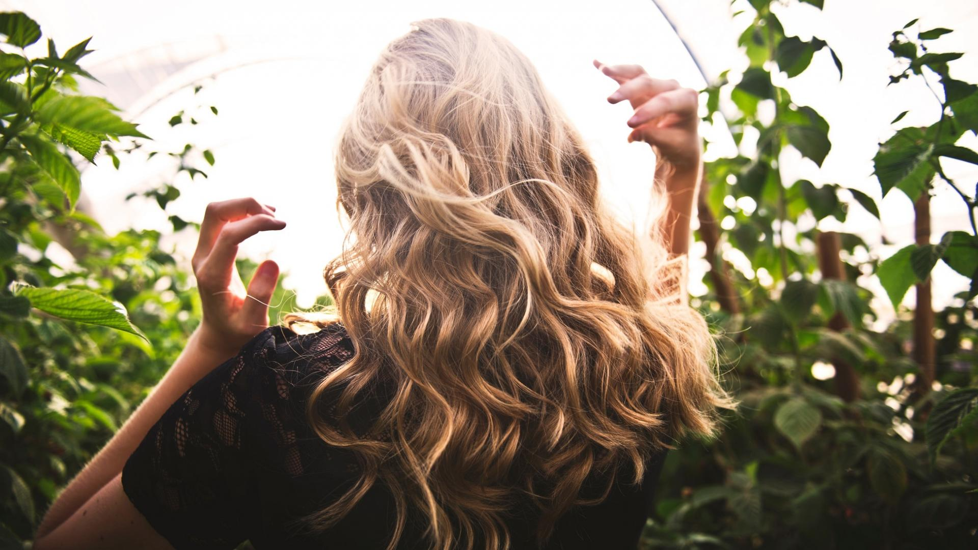 Frau mit blonden Haaren im Garten