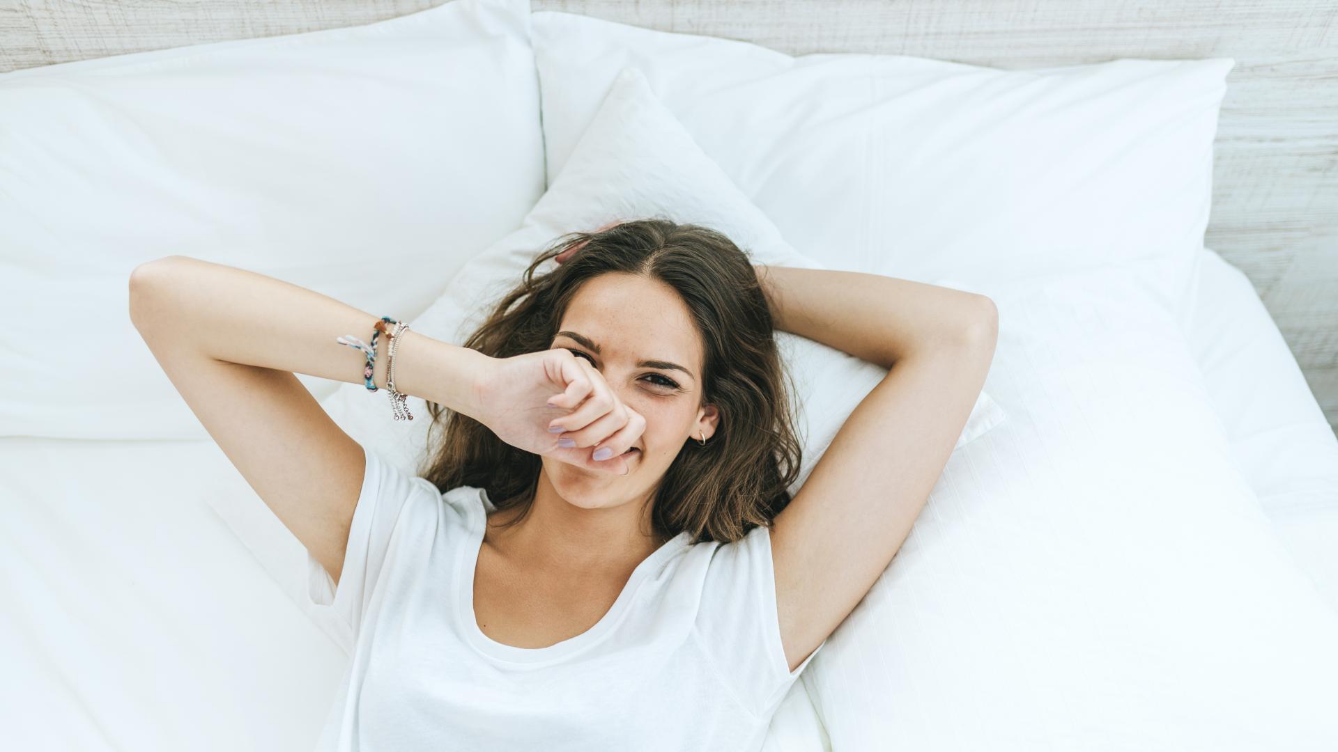 junge glückliche Frau im Bett mit weißem T-Shirt