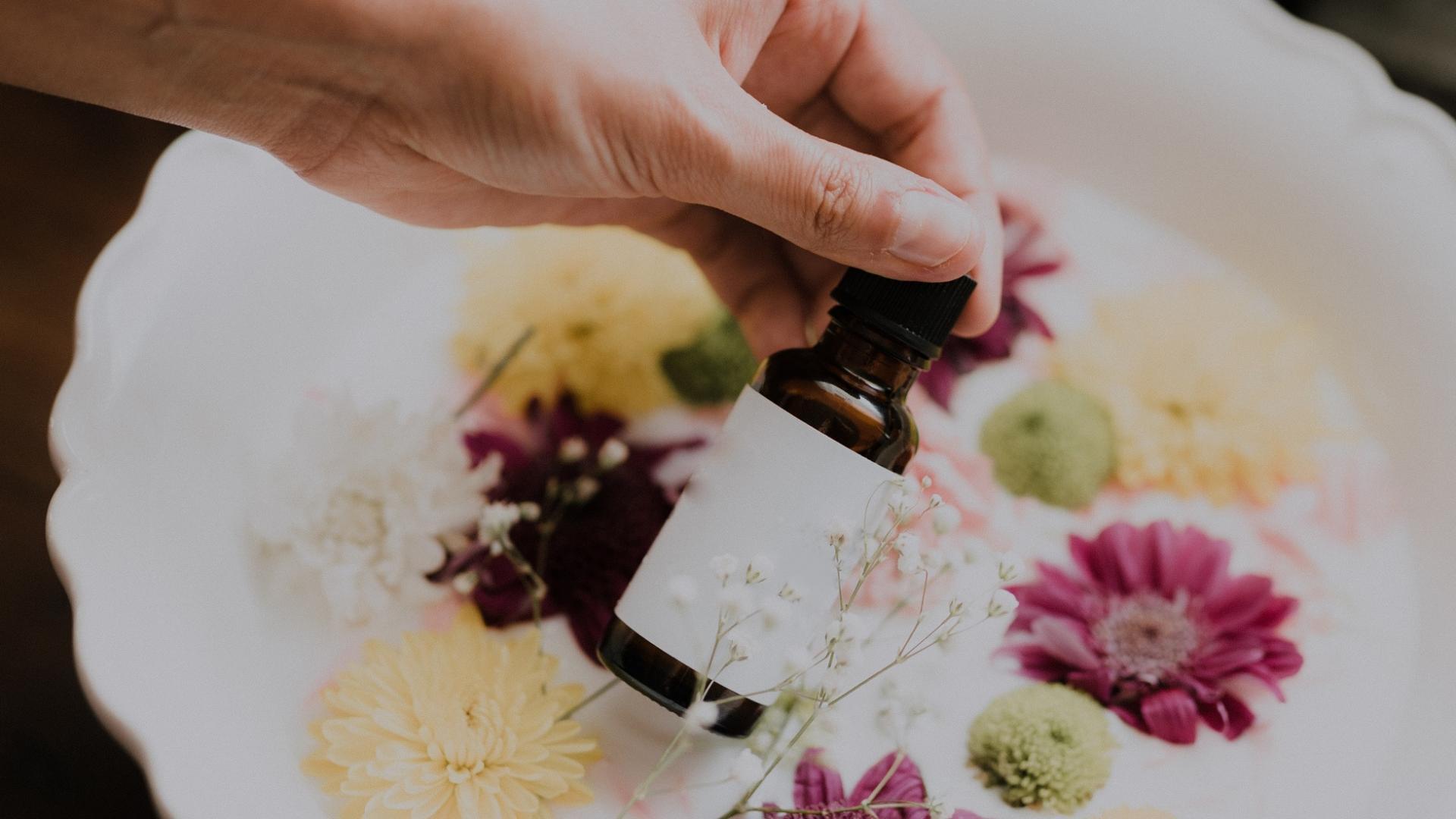 Hand hält Öl vor einer Schüssel mit Blumen