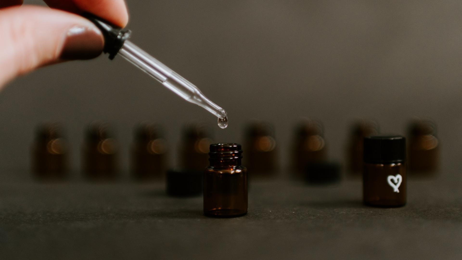 Hand hält Pipette und lässt Öl in kleines Fläschchen tropfen