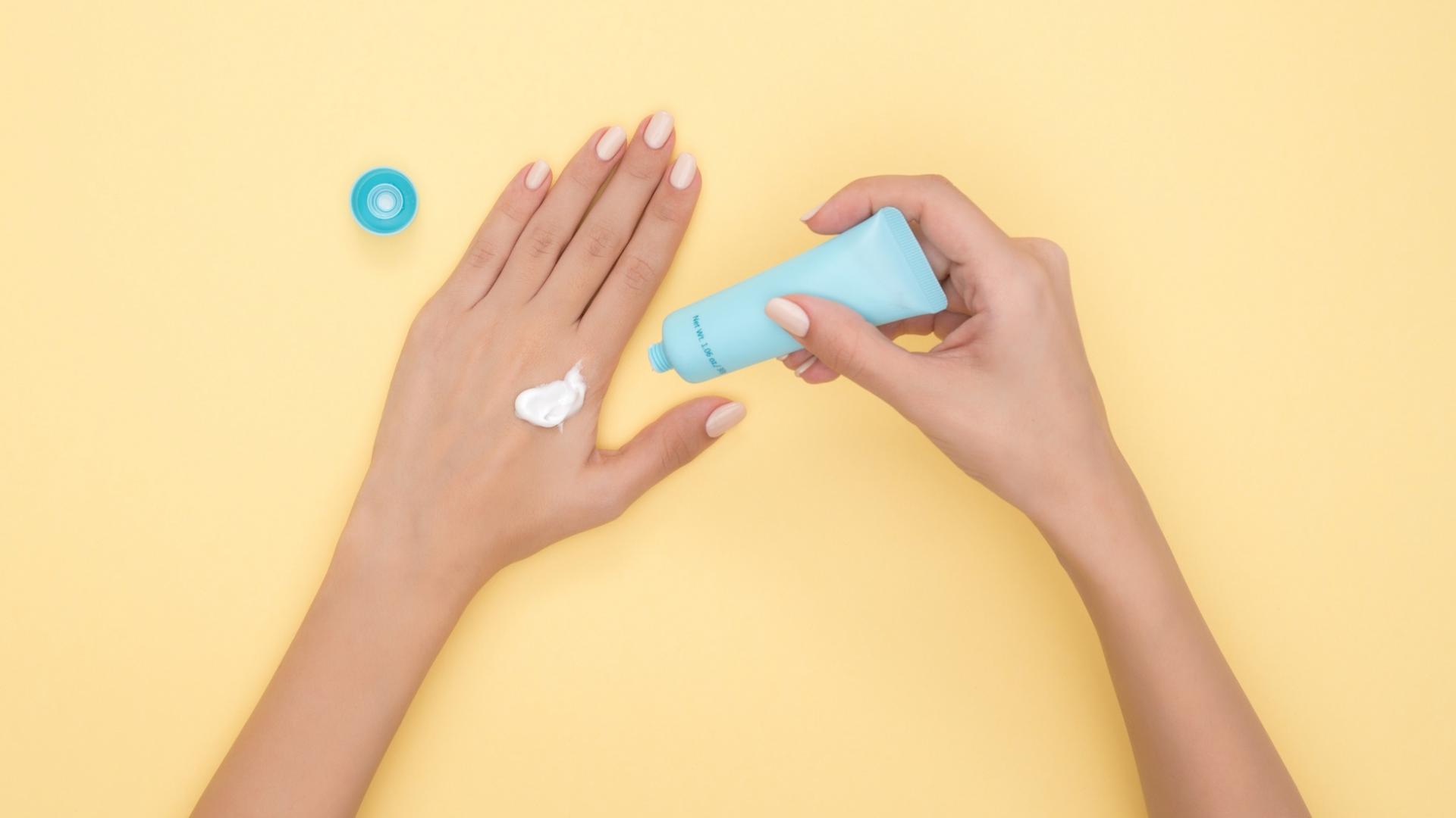 Hände vor einem pastellgelben Hintergrund mit einer Cremetube