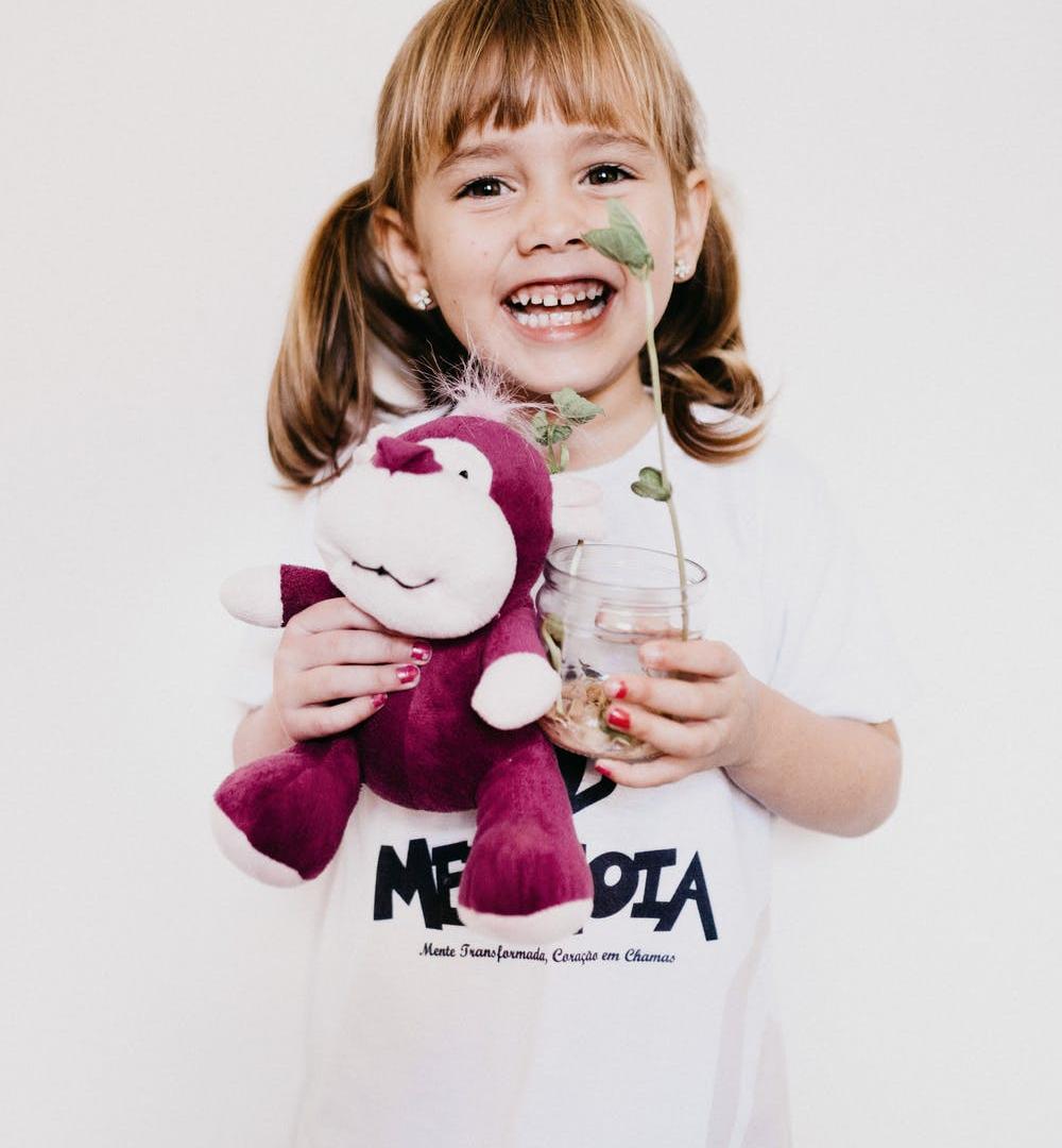 Kind mit Teddy und Blume
