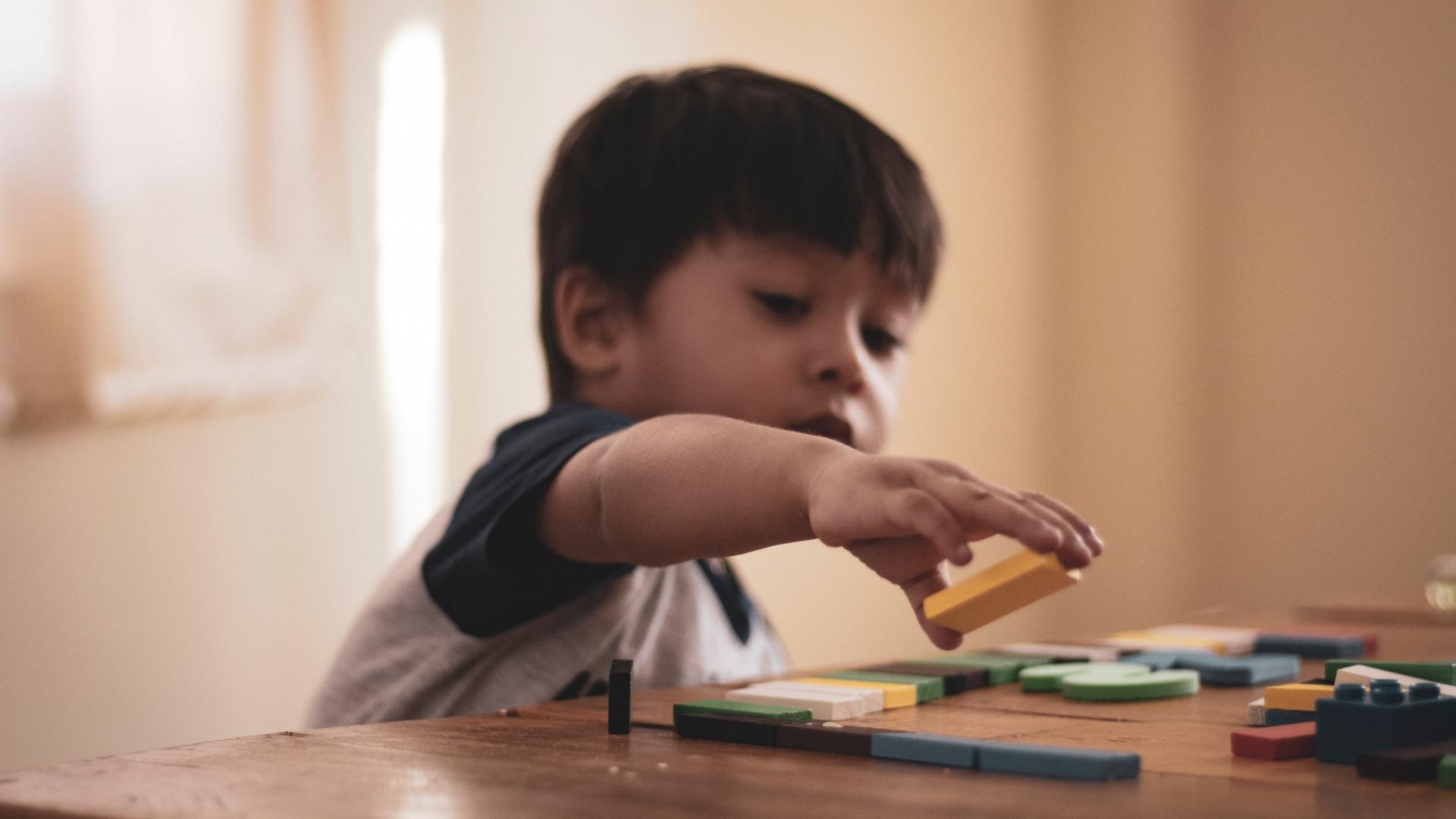 Junge spielt mit Holz