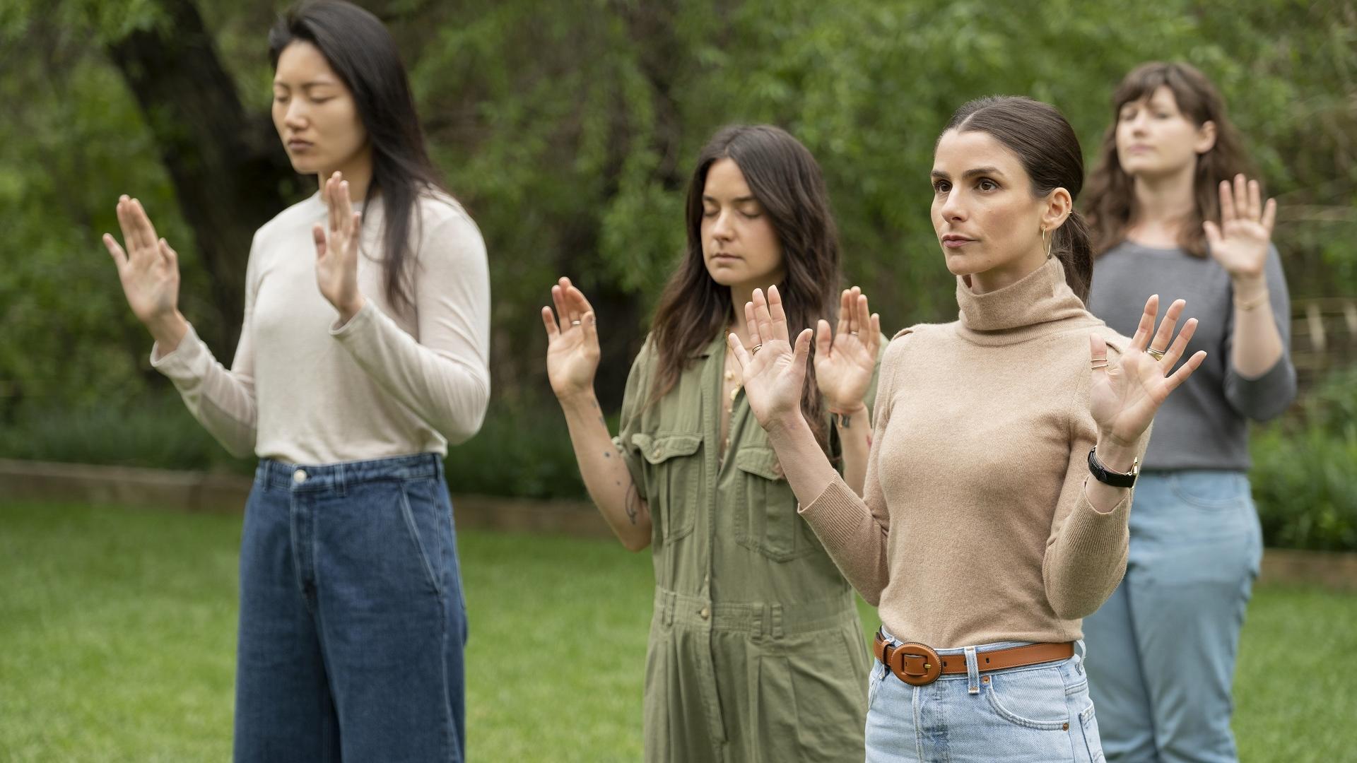 Junge Frauen stehen mit hochgereckten Armen und teils geschlossenen Augen im Park