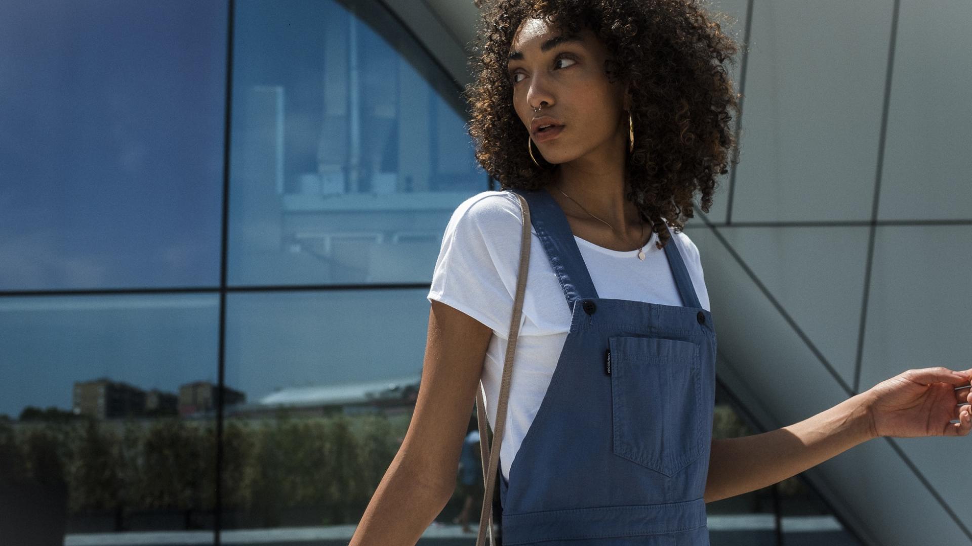 junge Frau mit Afro-Locken und modischer Kleidung vor einem Gebäude