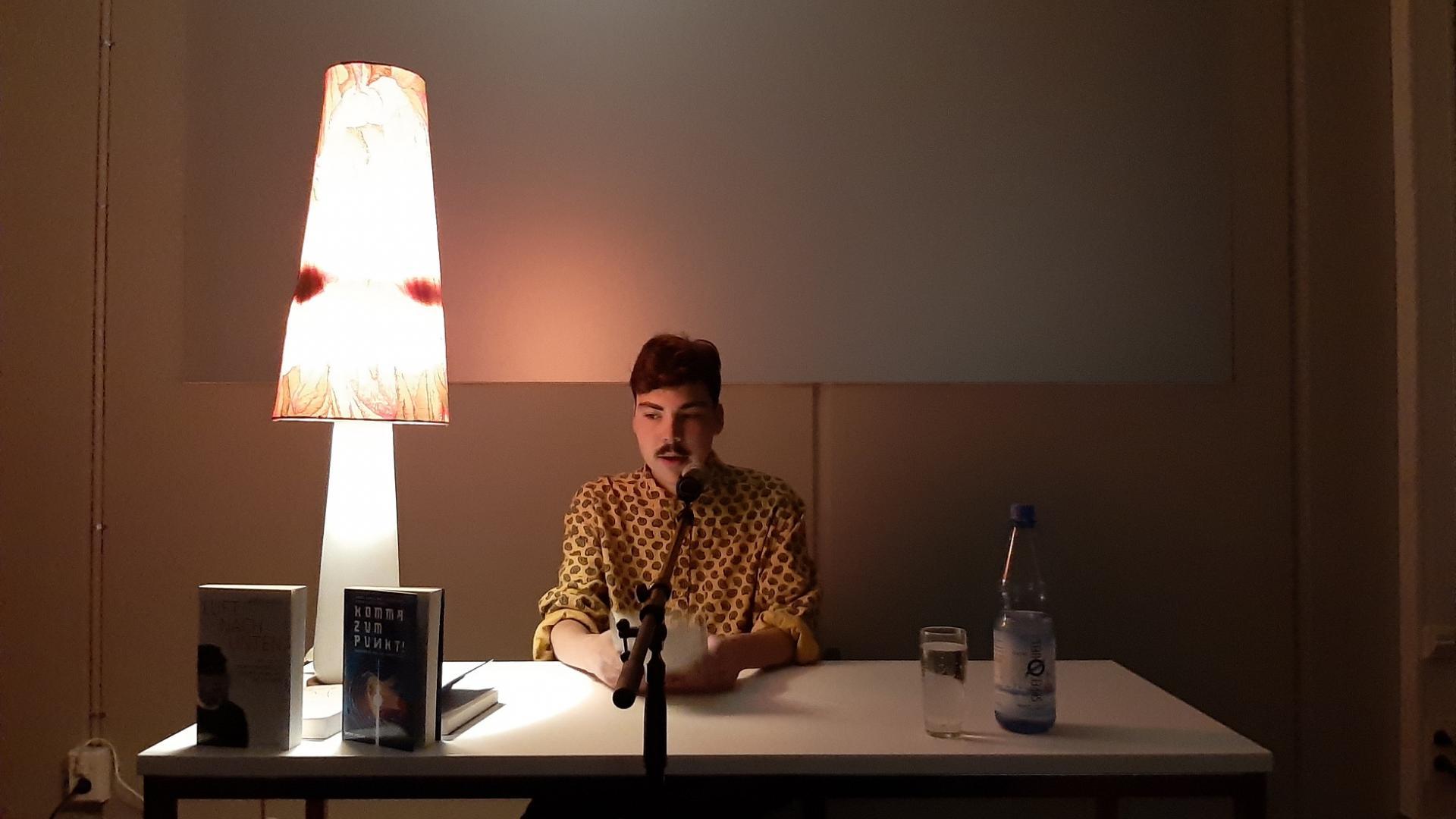 dunkelhaariger Mann liest Buch am Tisch