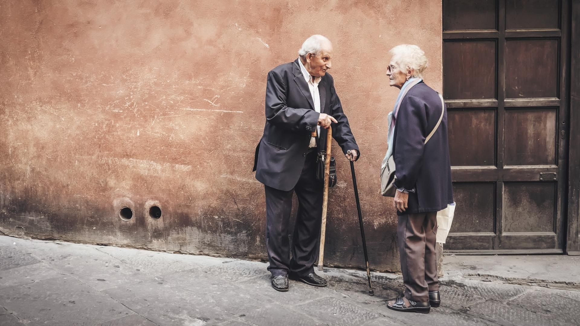 älterer Herr und ältere Frau mit weißen Haaren und Krückstock vor einer Hauswand