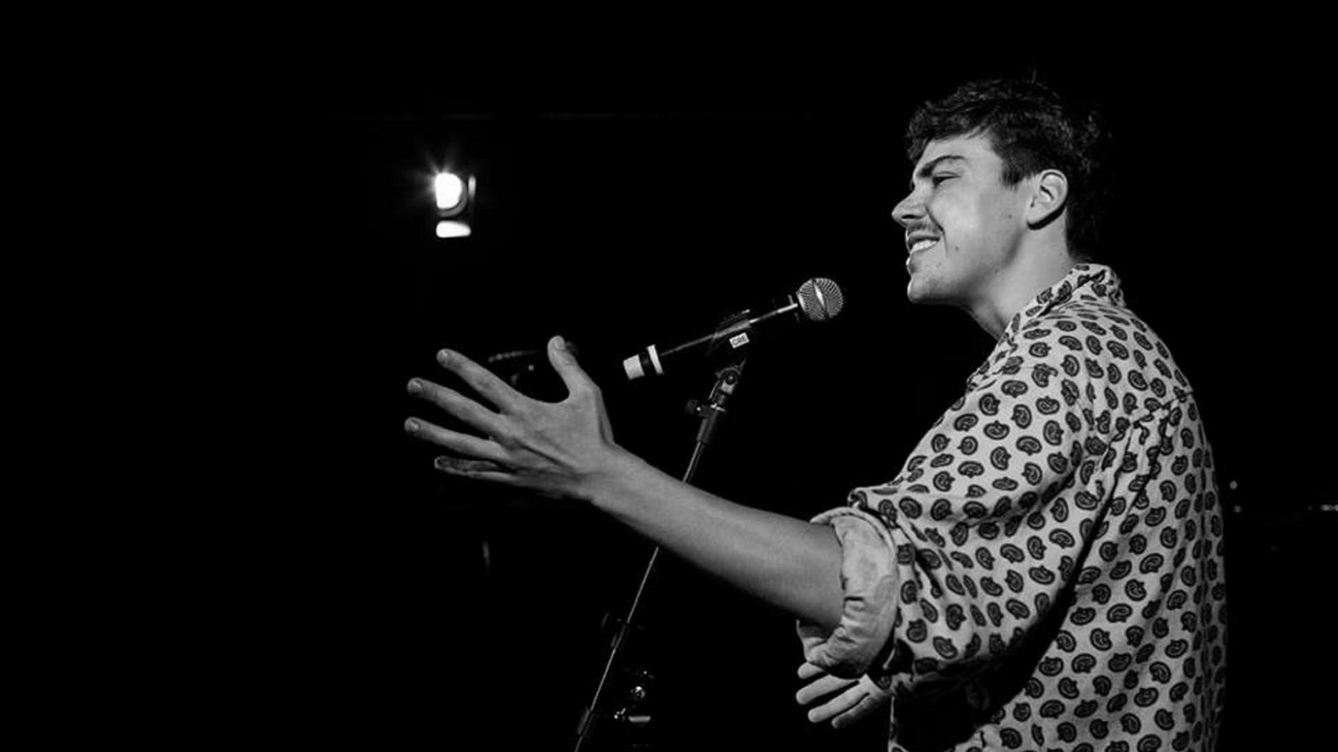 schwarz-weiß Fotografie von dunkelhaarigem lachendem Mann vor dem Mikro