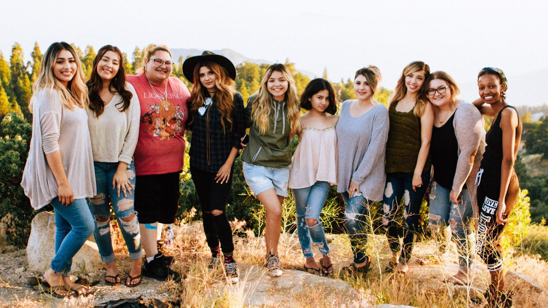 Lachende Frauen unterschiedlicher Herkunft und mit unterschiedlichen Kröperformen auf einer Wiese